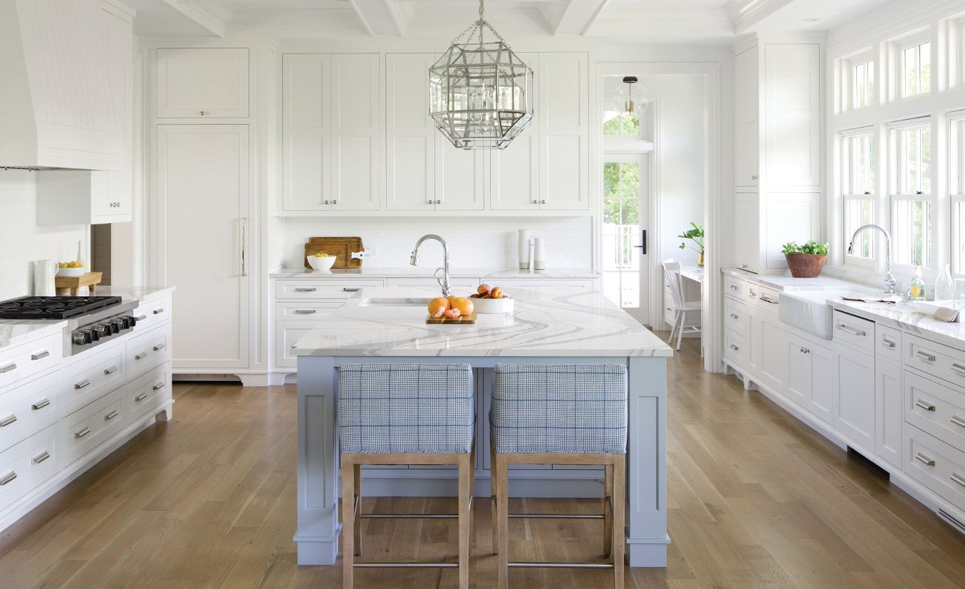 White kitchen with light blue-gray island and Cambria Brittanicca countertops.