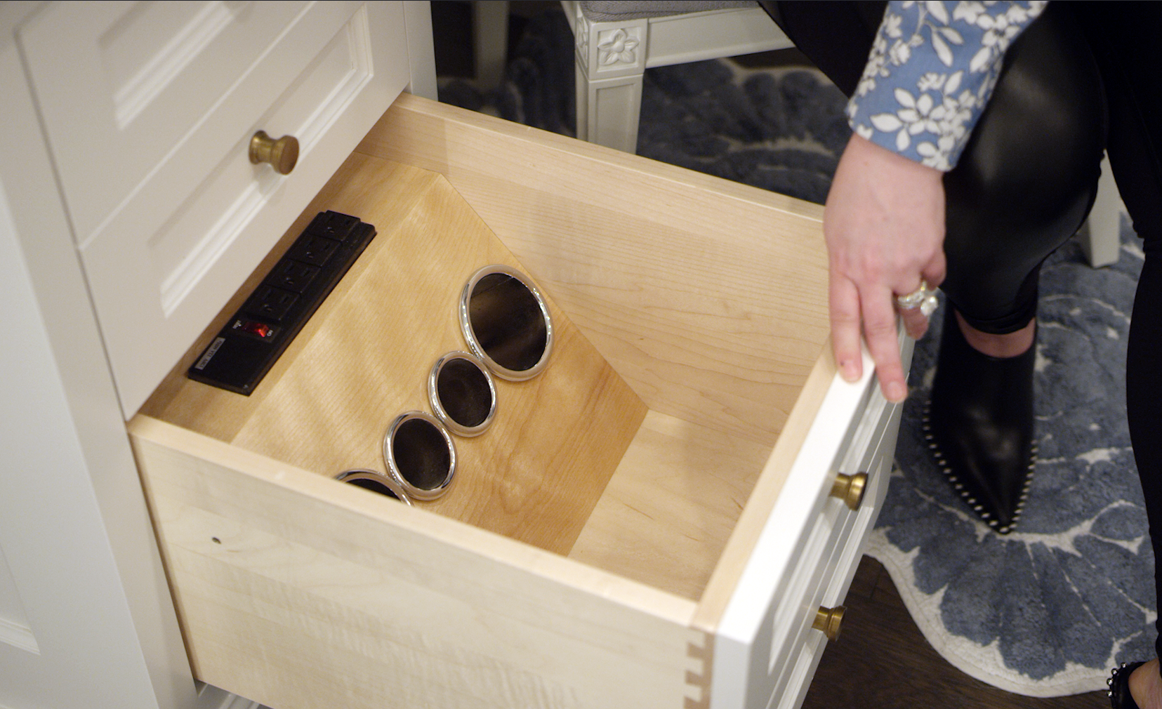 Carly Zucker shows the inside of a drawer with custom holder for hair styling tools.