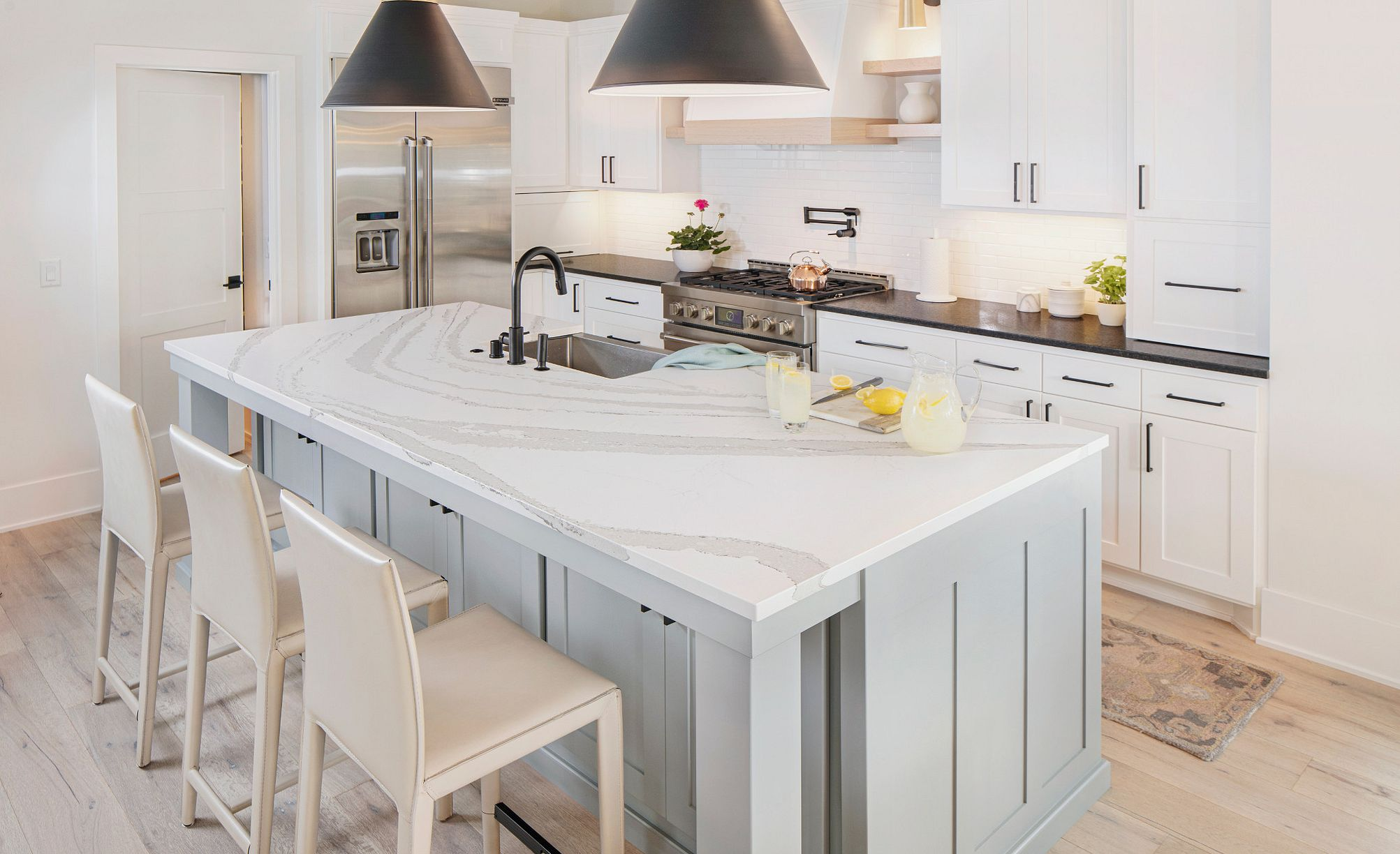 White marble-look quartz countertops in paired with matte black accents and two-tone cabinets.