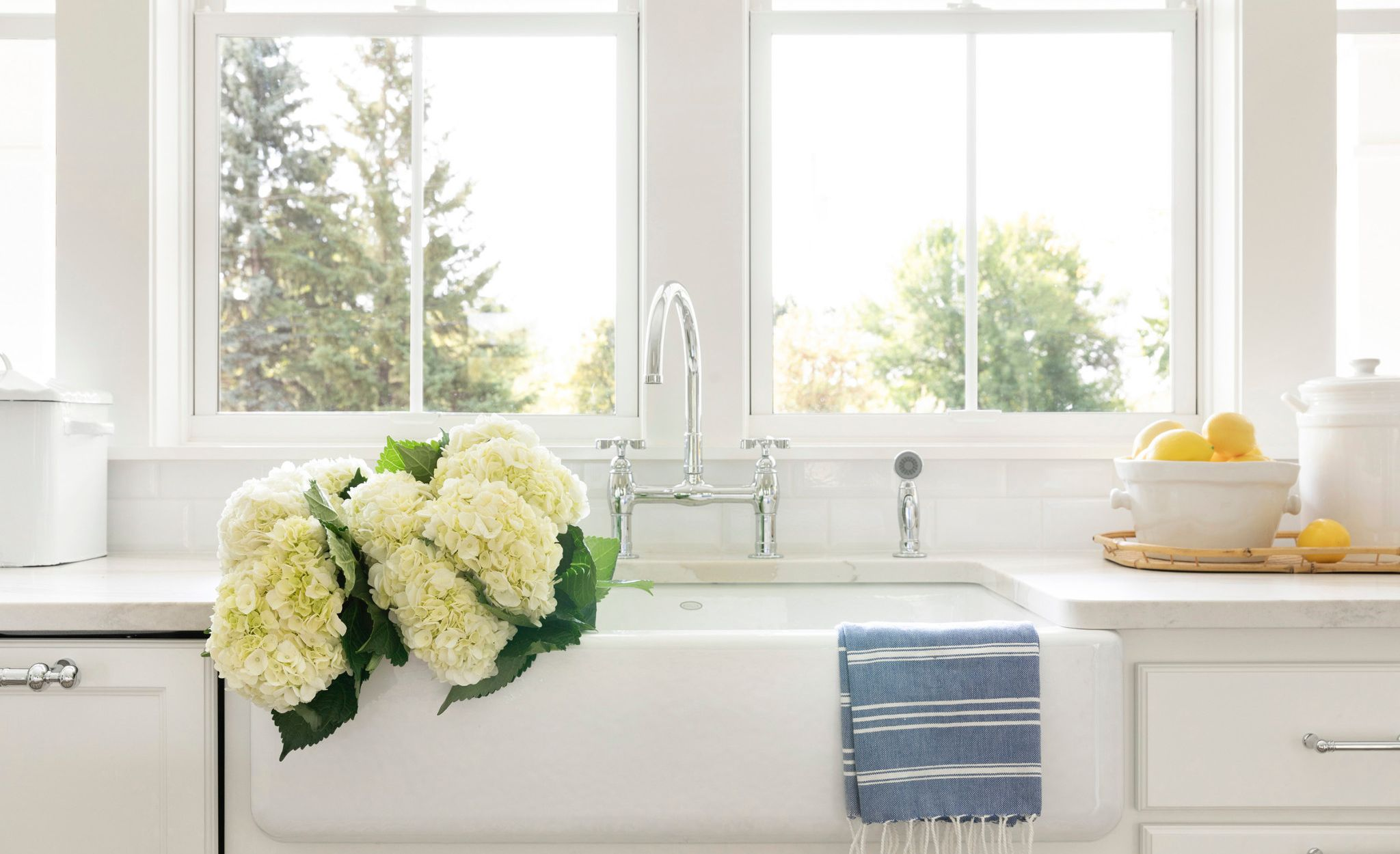 A stunning, white farmhouse sink pairs beautifully with Brittanicca Warm.