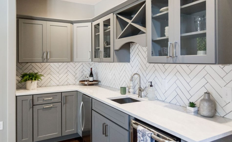 Cambria Delgatie countertops paired with herringbone tile and gray kitchen cabinets.