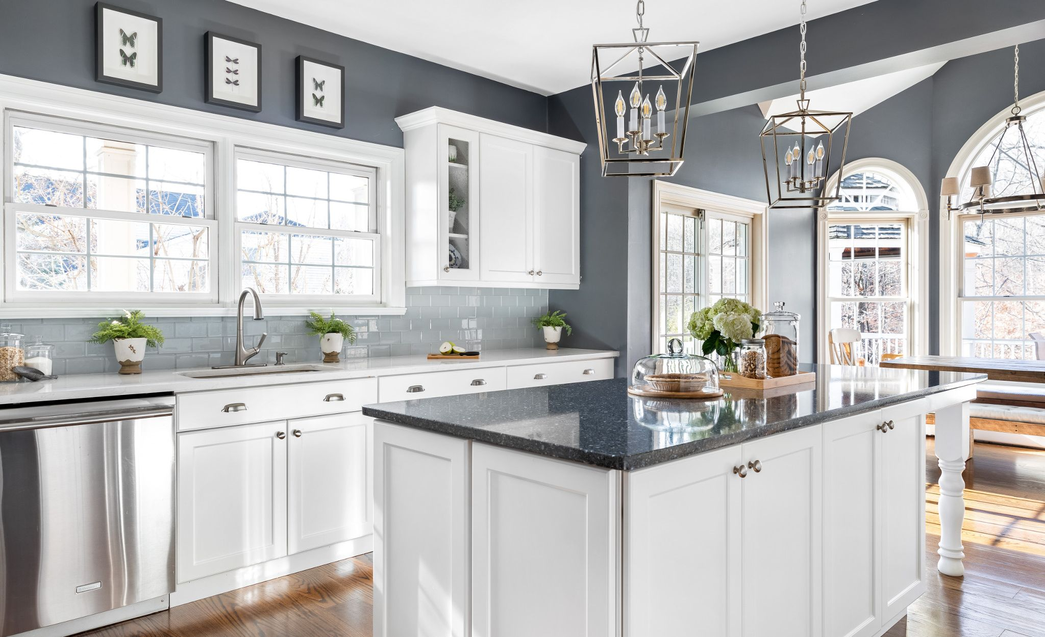 Dark blue kitchen island featuring Cambria Parys paired with a Cambria Swanbridge perimeter countertops.