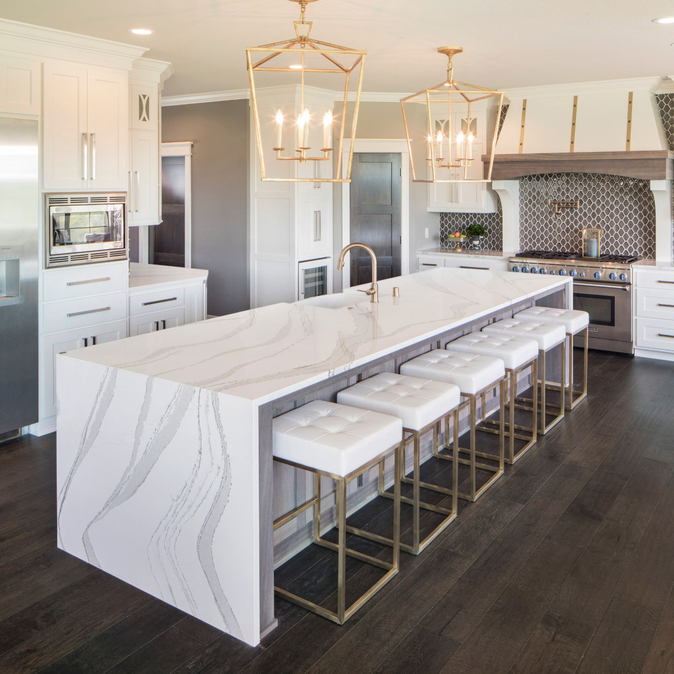 White marble-look quartz countertops in a white and gold kitchen.