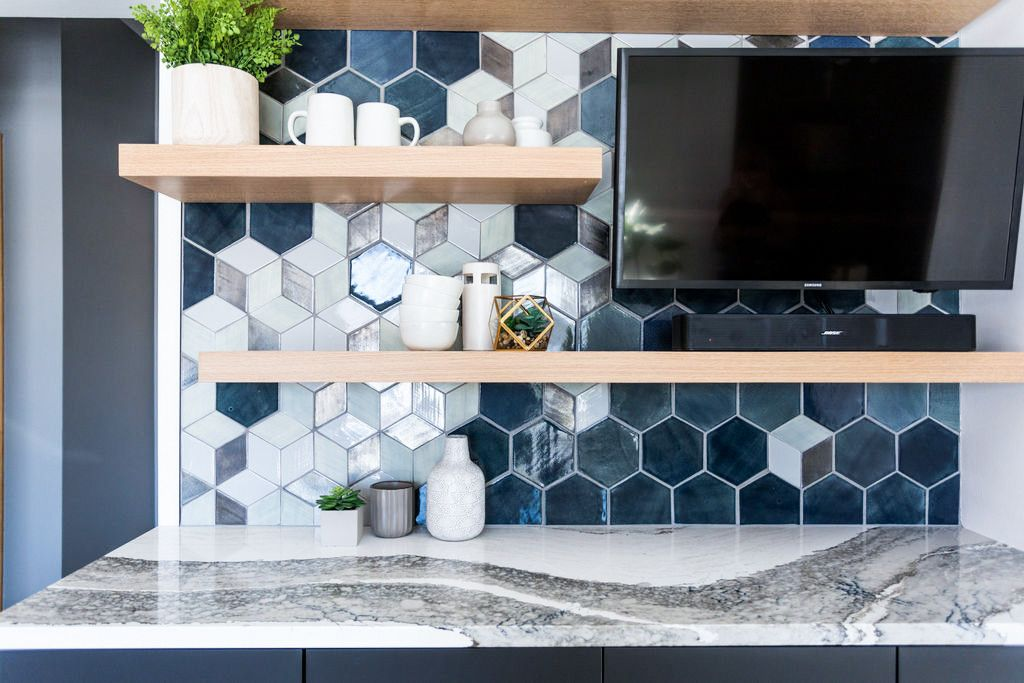A kitchen and dining space bar with Cambria Skara Brae countertops and a backsplash created by Mercury Mosaics.