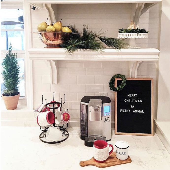 Cake stands and Christmas mugs create a cozy holiday moment.