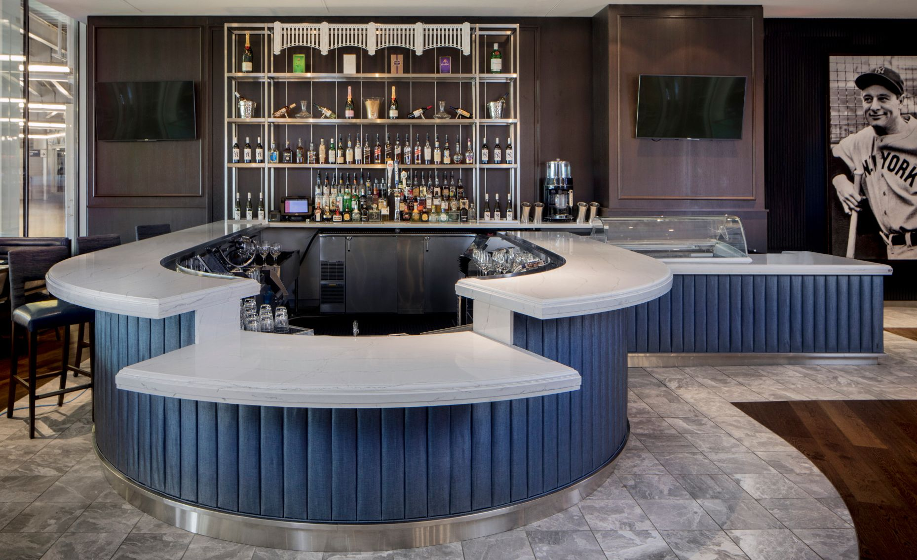 Rounded blue and white bar featuring Ella countertops is one of many stunning Cambria spaces that inspires sports fans.