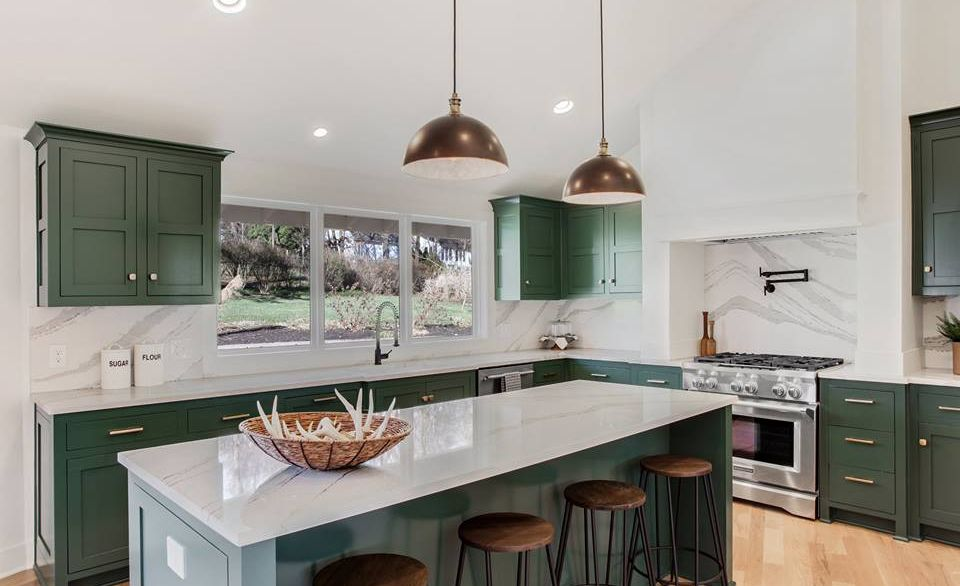 Cambria Brittanicca™ backsplash and countertops contrast emerald green cabinets in this chic farmhouse kitchen.
