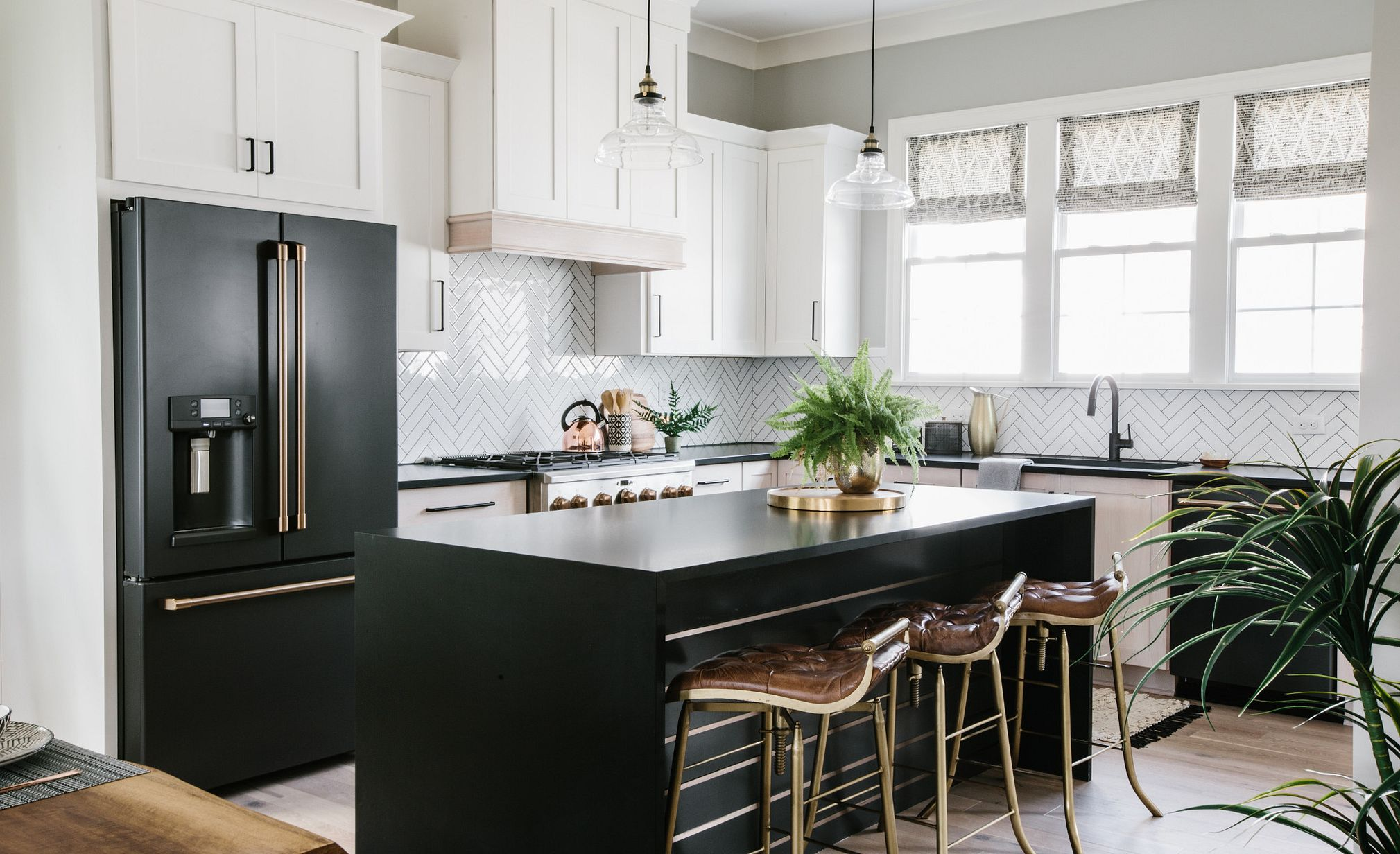 This spacious open kitchen offers optimal traffic flow and properly scaled details, including a Cambria Blackpool Matte waterfall-edge island.