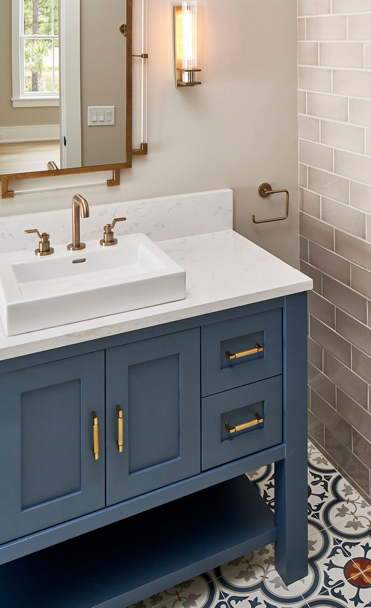 A blue vanity compliments Cambria Torquay and a mosaic tile.
