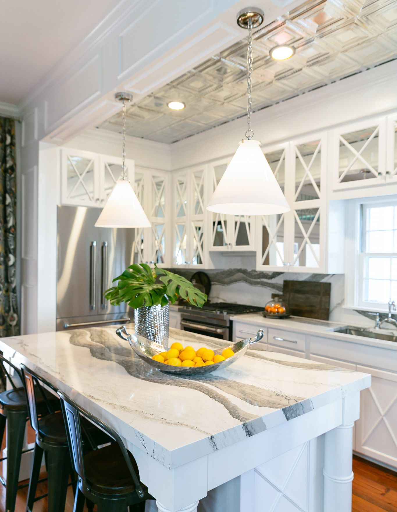 A white kitchen with mirrored cabinet doors with Cambria Skara Brae countertops and backsplash.