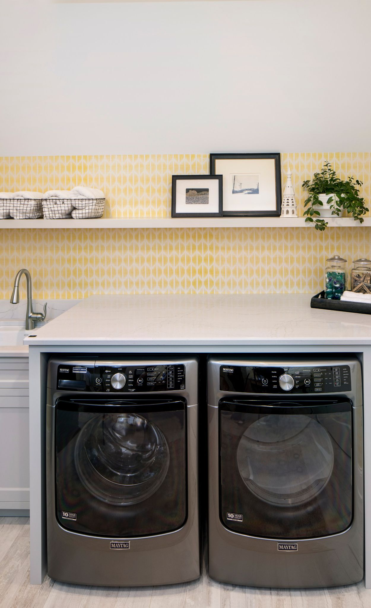 Cambria Ella in a laundry room with yellow wallpaper.