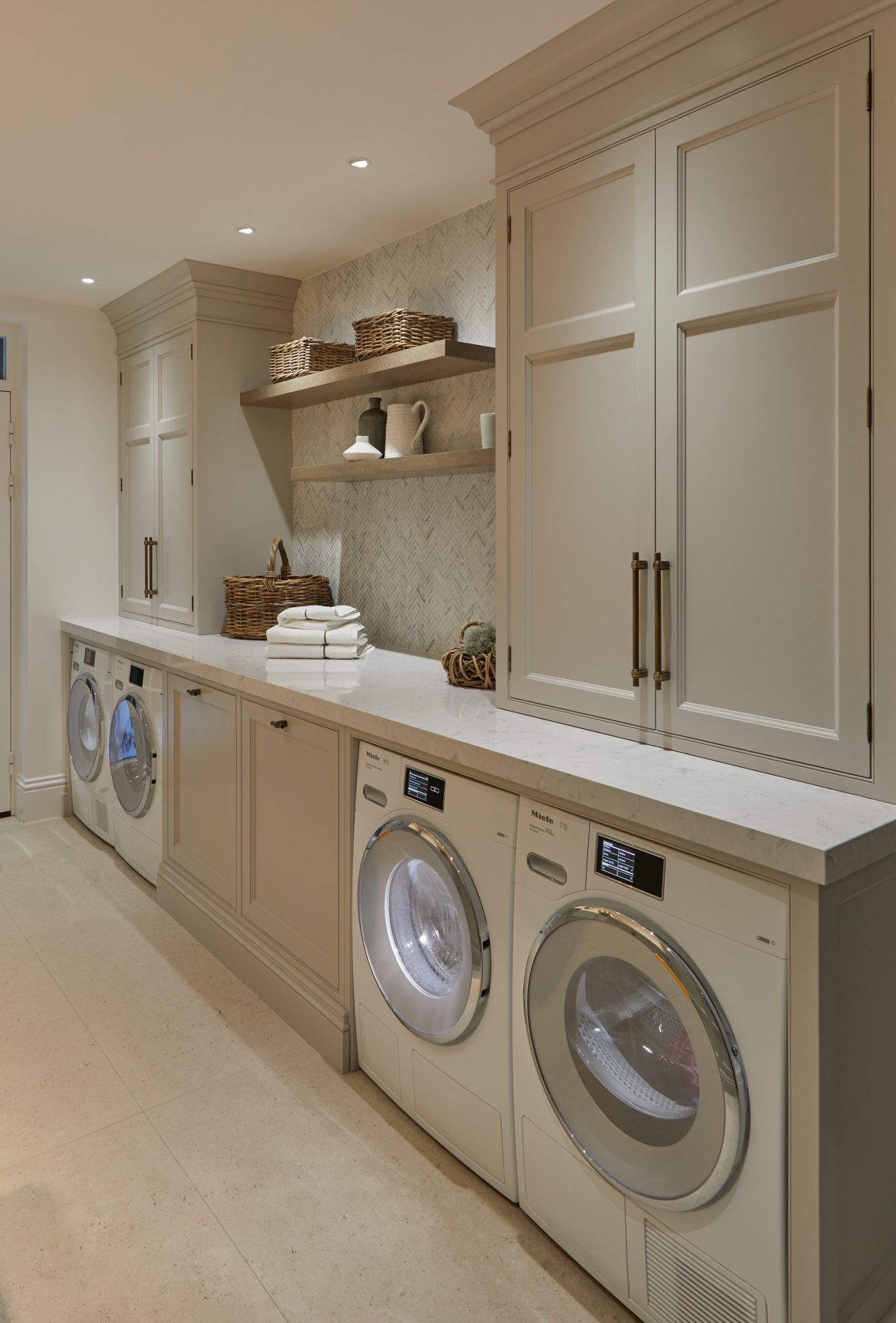 A second view of a laundry room with cream cabinets and marble chevron tile paired with Camrbia Swanbridge countertops.