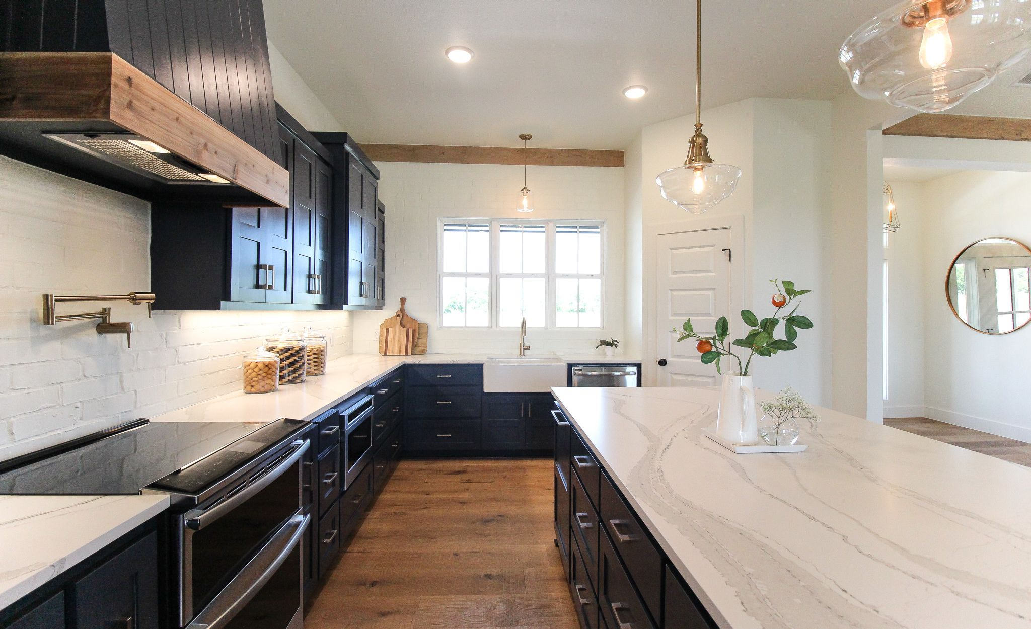 White marble-look quartz countertops paired with navy cabinets and white brick backsplash.