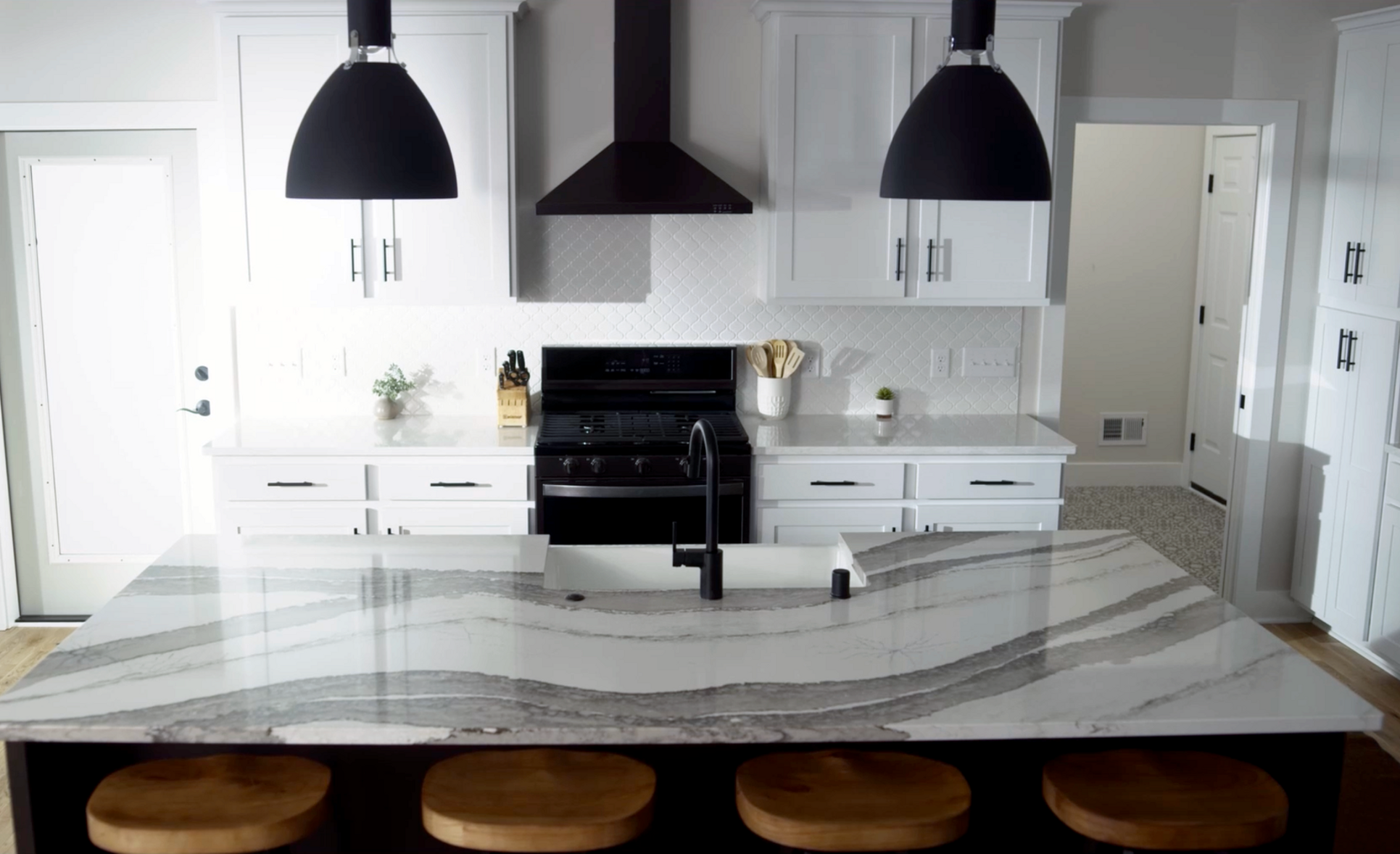 A white kitchen features Cambria Skara Brae and Ironsbridge with black appliances and lighting.