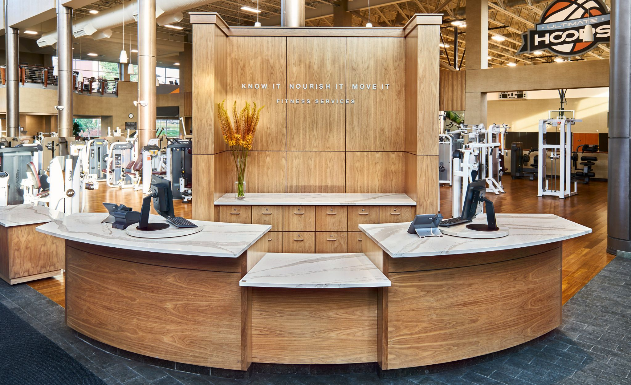 Reception desk featuring Cambria Brittanicca Warm countertops at Life Time fitness.