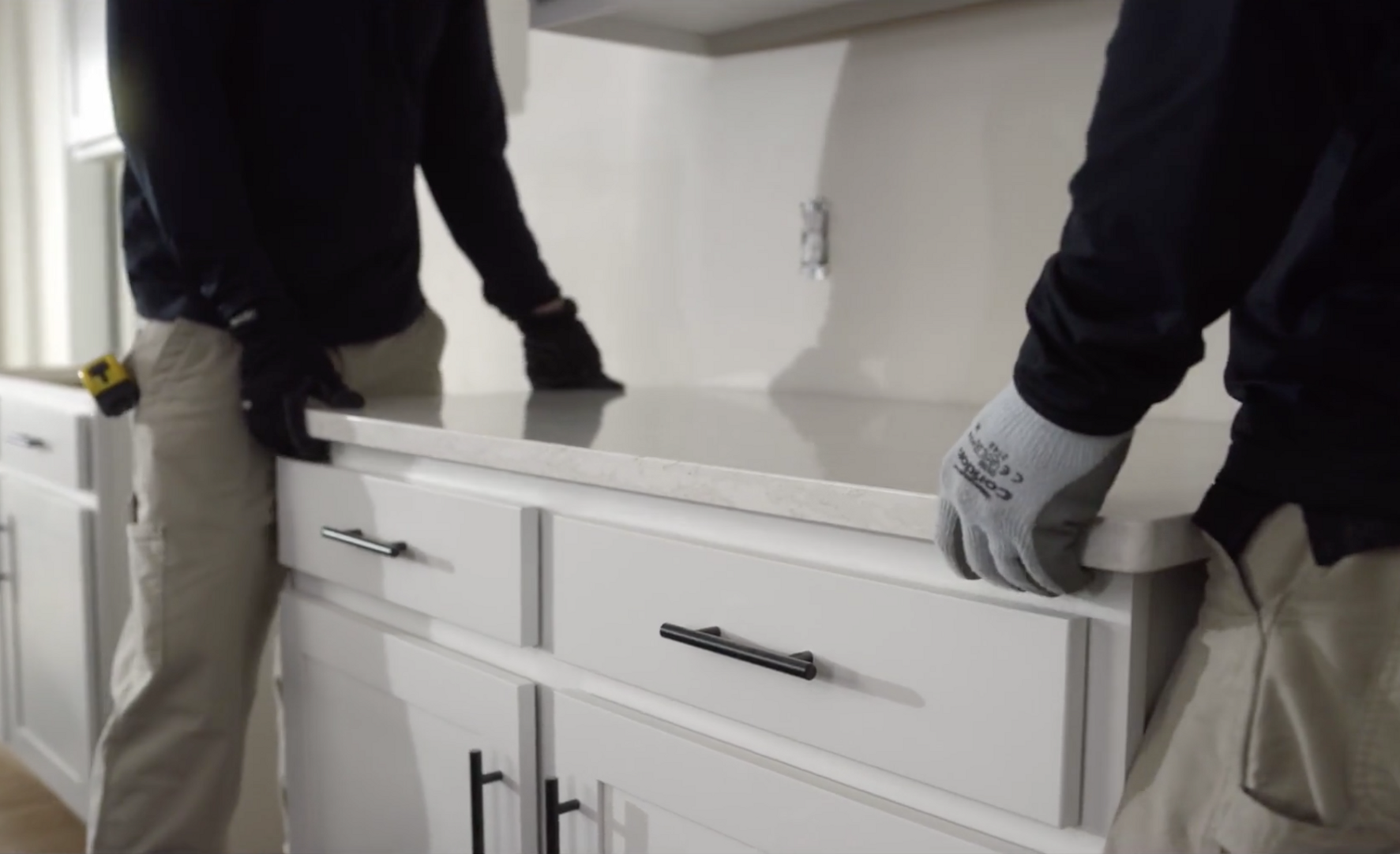 Two installers place a Cambria countertop onto a white cabinet for install.