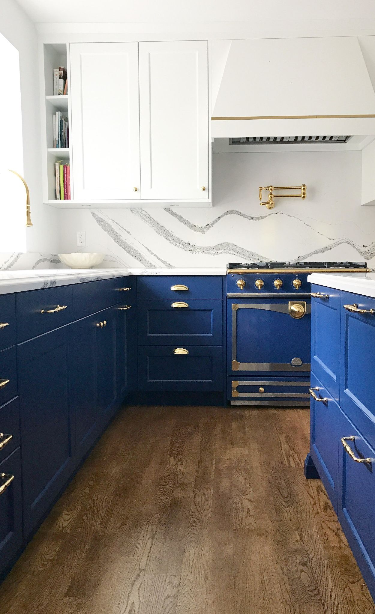 Blue cabinets and blue appliances paired with Cambria Annicca countertop and backsplash.