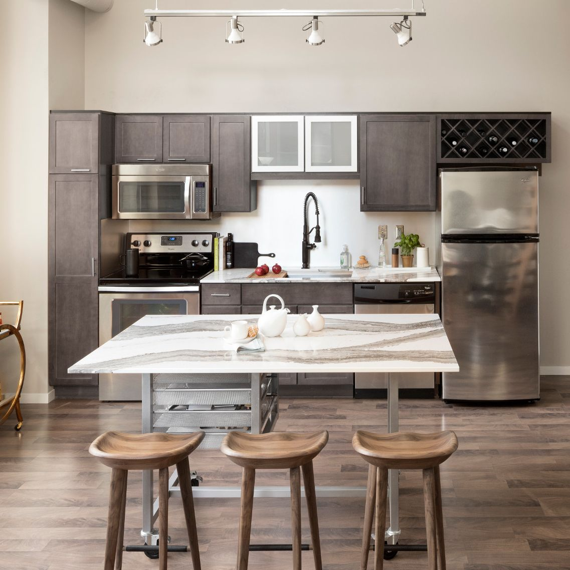 A sleek warm toned kitchen with brown cabinets and a mobile metal island with Cambria Skara Brae countertops.