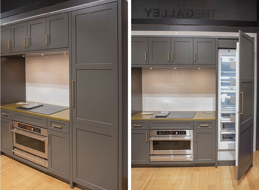 Sleek gray cabinetry with a hidden refrigerator by Harmoni.