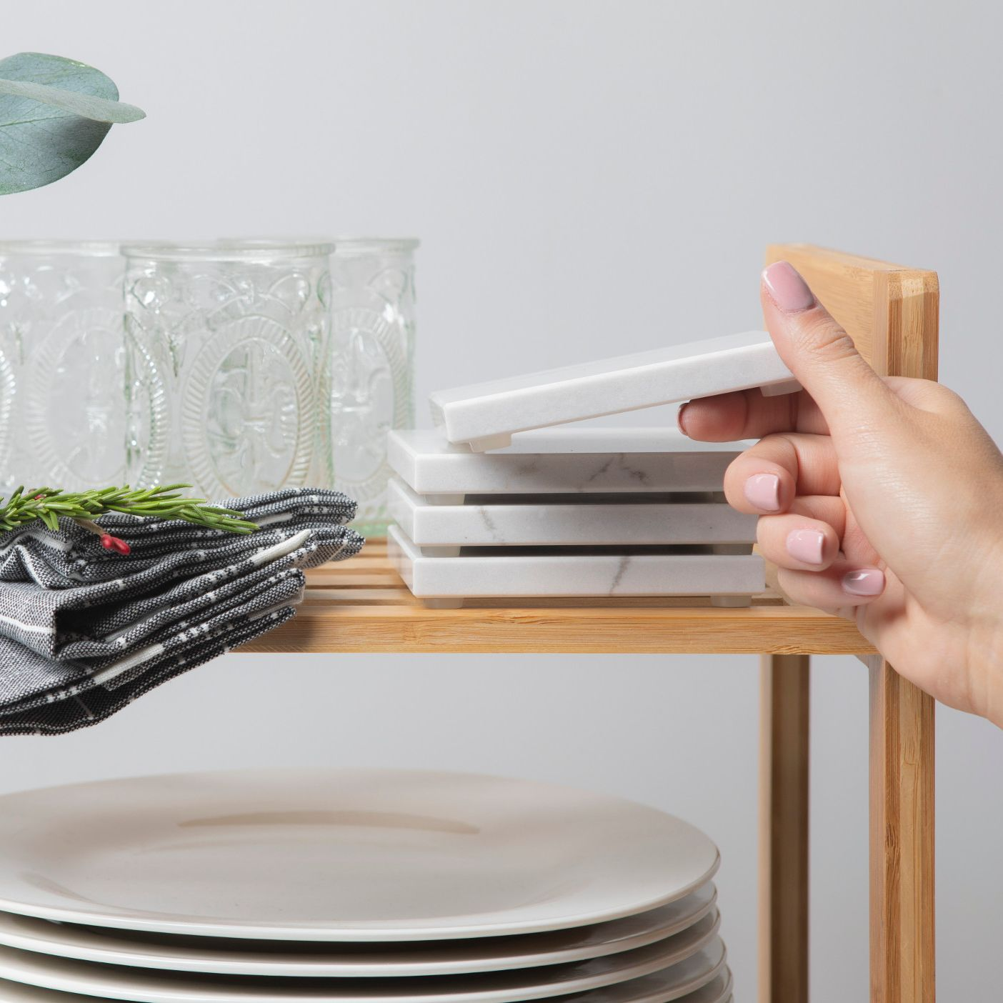 Cambria coasters being stacked on a shelf.