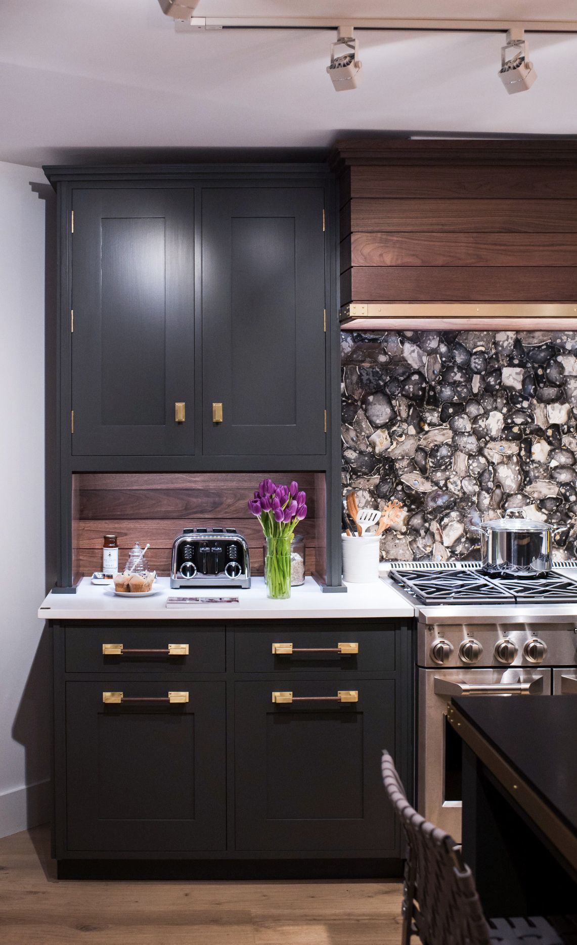 A custom mosaic of English flint pairs well with olive green cabinets, walnut, and Cambria White Cliff Matte.