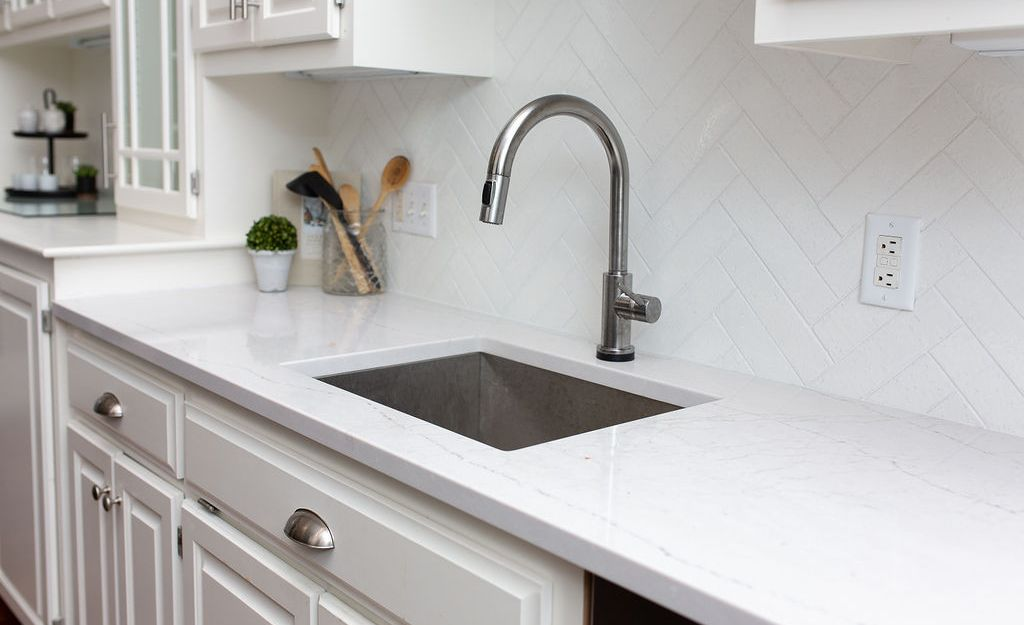 Cambria Ella countertops paired with white herringbone tile.