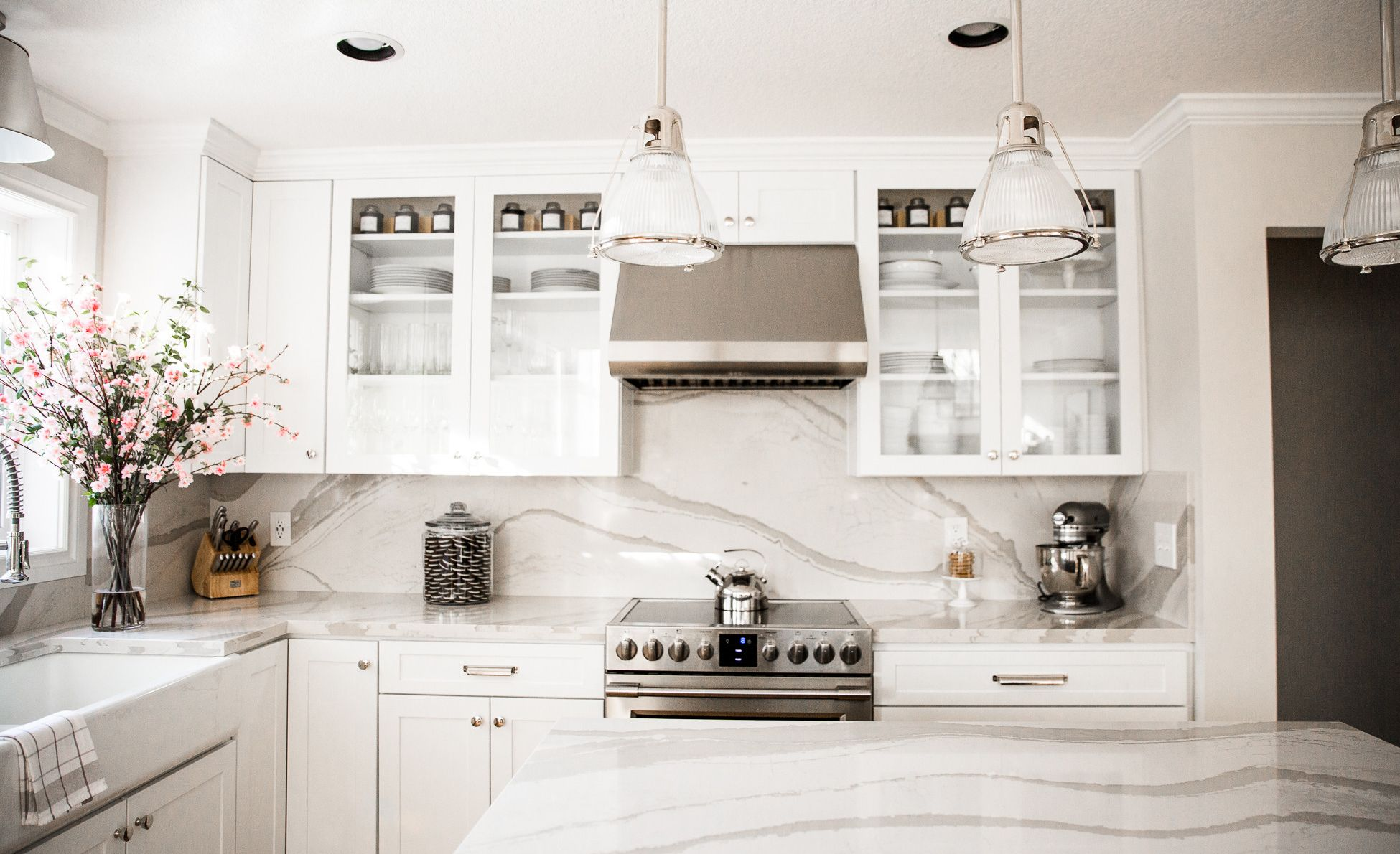 White marble-look quartz countertops in paired with white and glass panel cabinets.