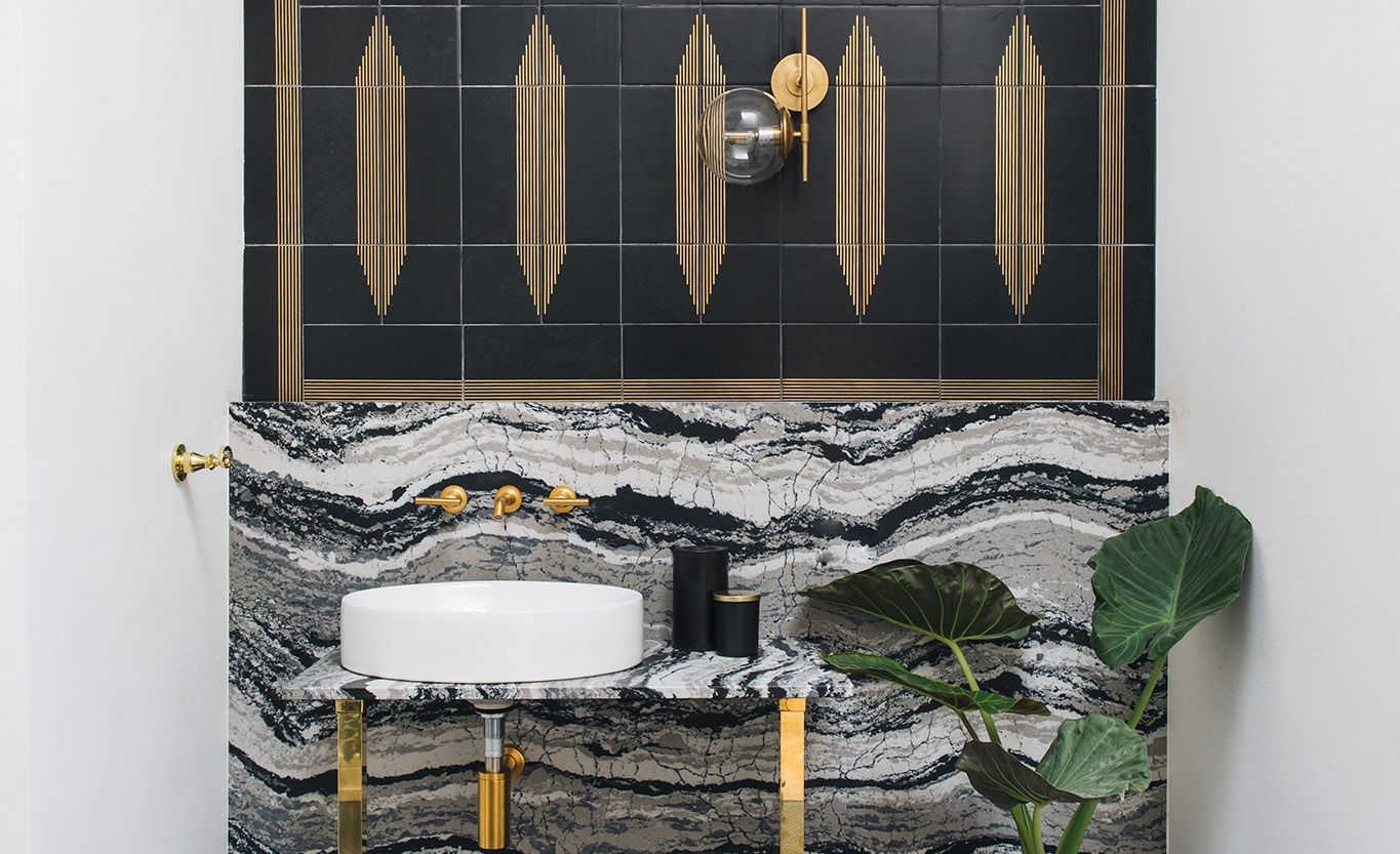 A Cambria Levven™ backsplash and vanity pairs with matte black and brass in this studio bathroom .