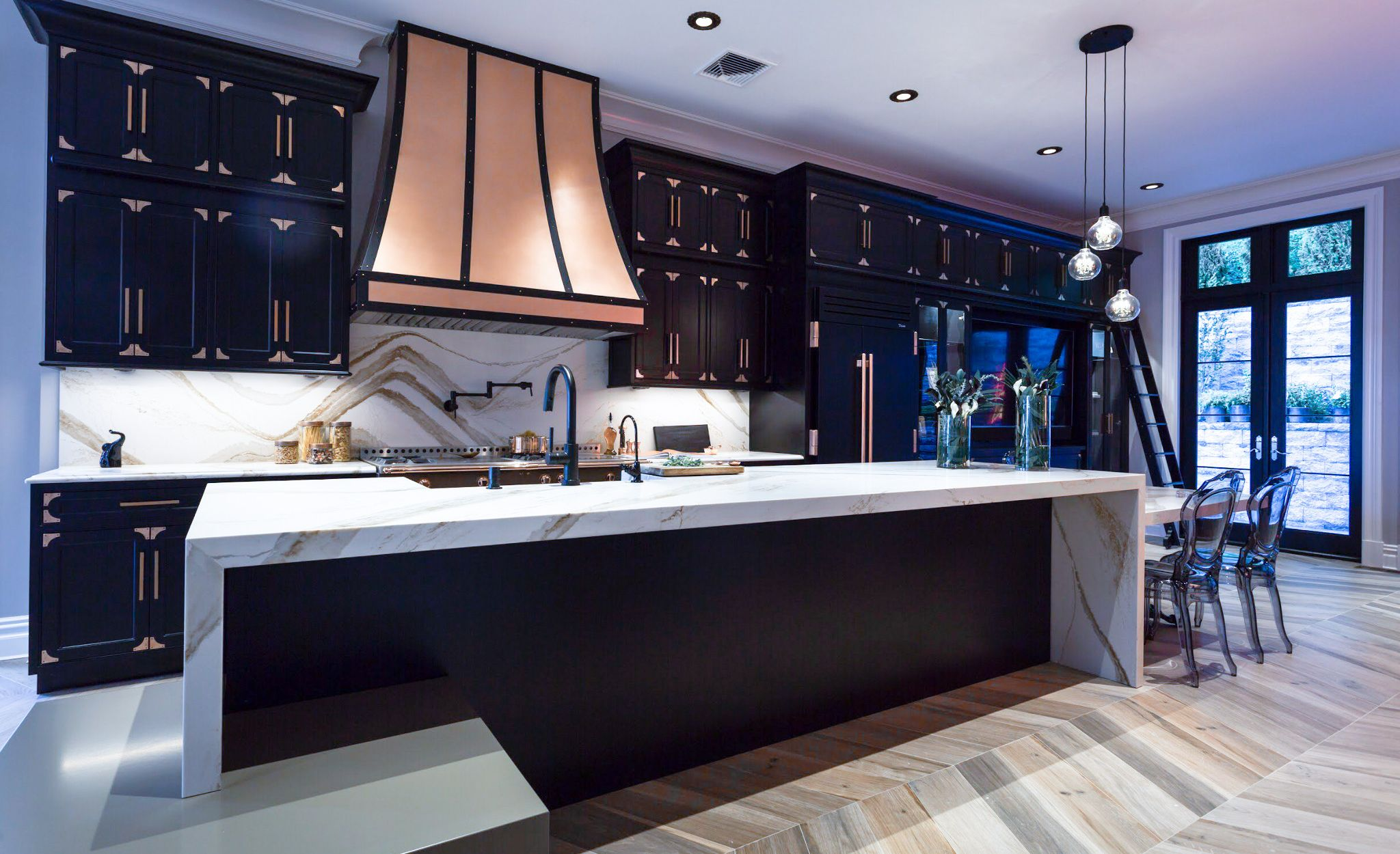 Gold marble-look quartz countertops in a black, high-contrast kitchen.