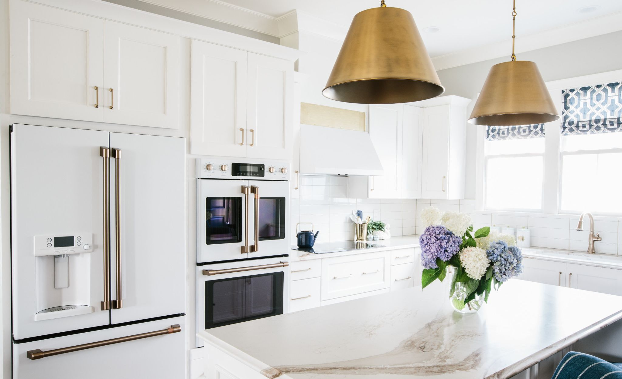 Cambria Brittanicca Gold in a white kitchen with coordinating white appliances and gold pendant lighting.
