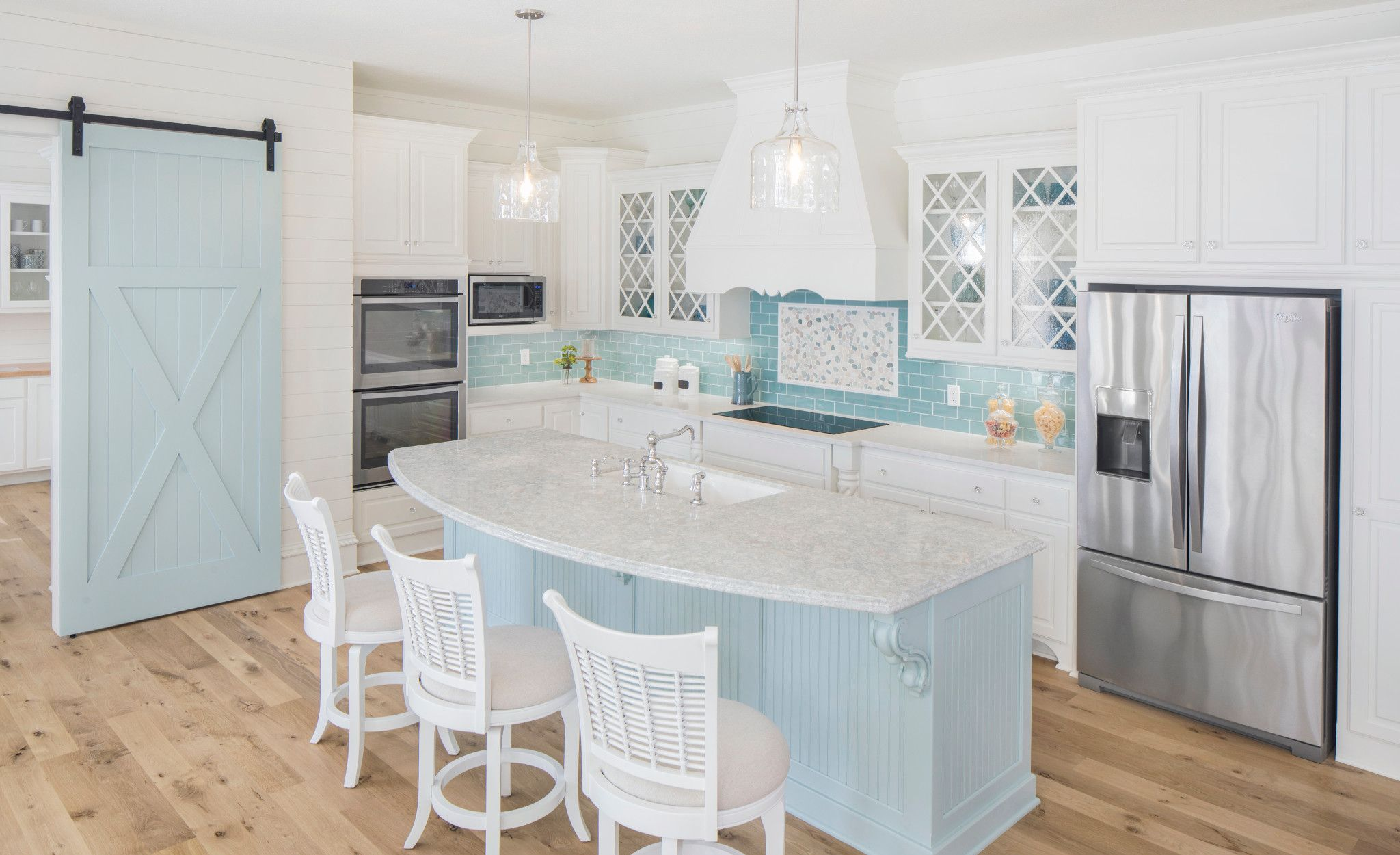 Coastal kitchen with pale blue island featuring Cambria Montgomery.