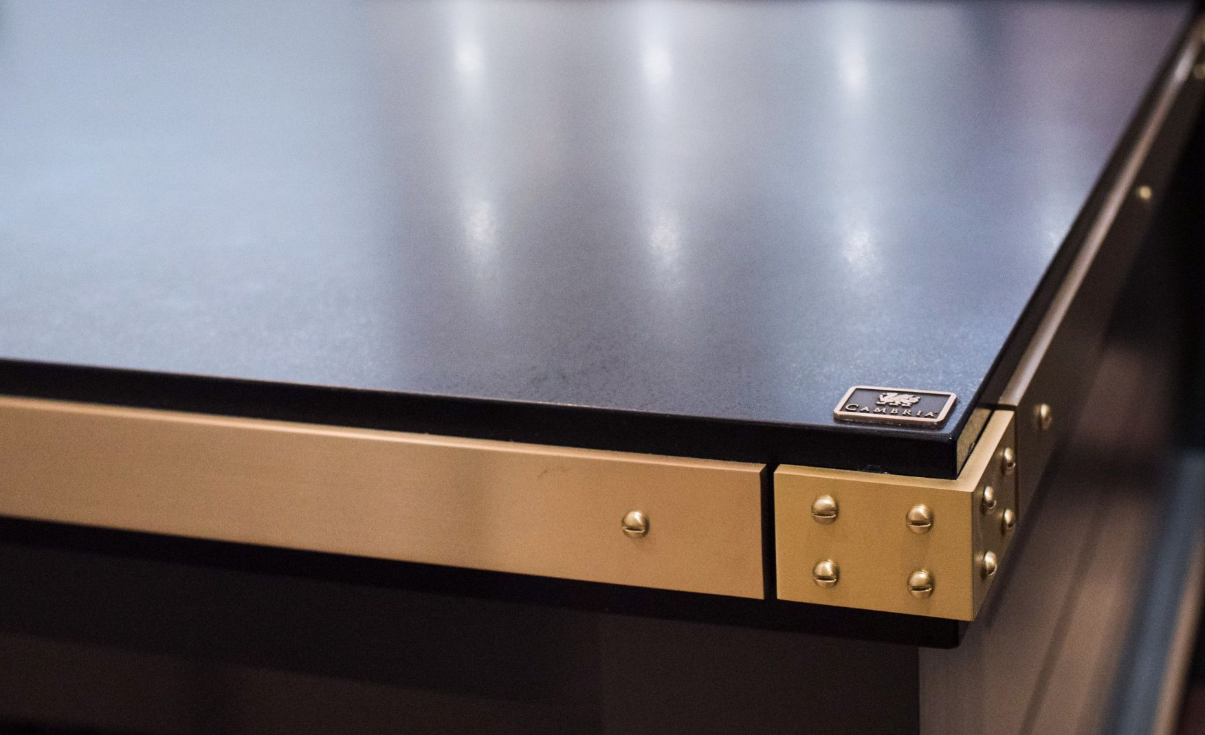 Cambria Blackpool Matte countertops with a brass band edge detail.