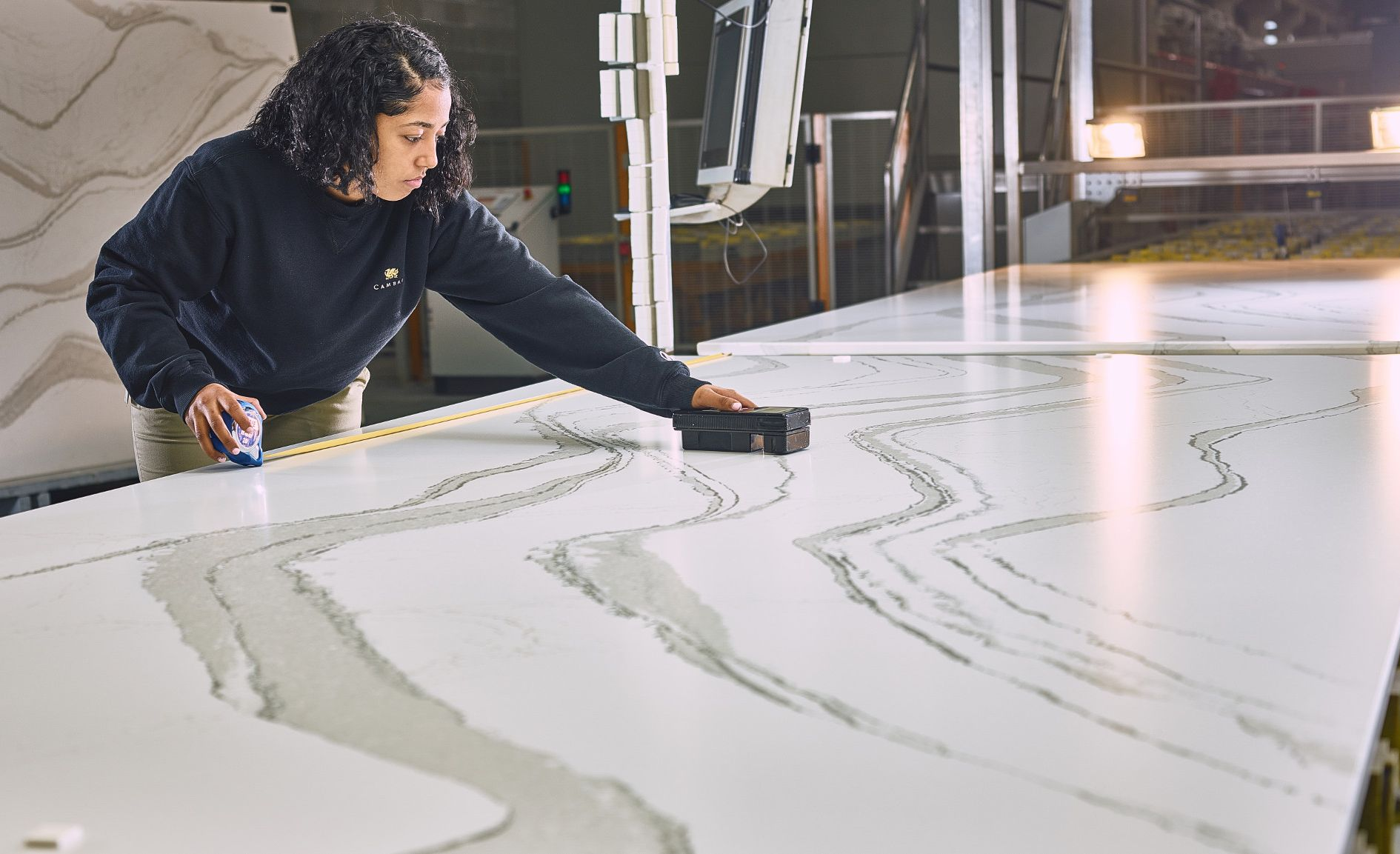 A Cambria employee uses a tool to measure gloss levels on a Cambria slab.