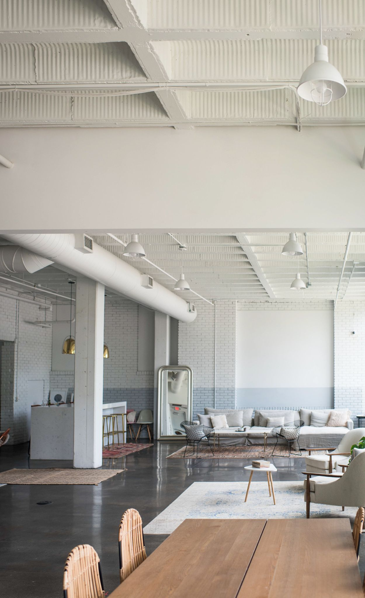 Exposed beams, pipes, and concrete flooring reflect the building's industrial roots.