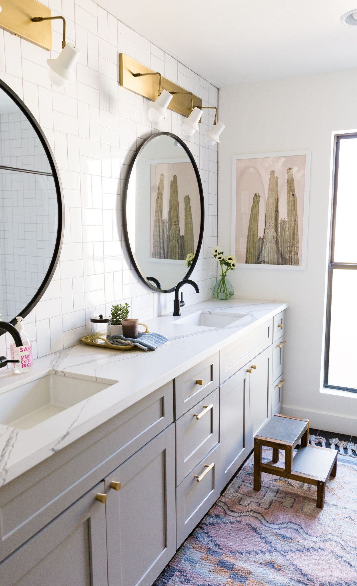 Dual black matte faucets and mirrors contrast with Brittanicca Matte™