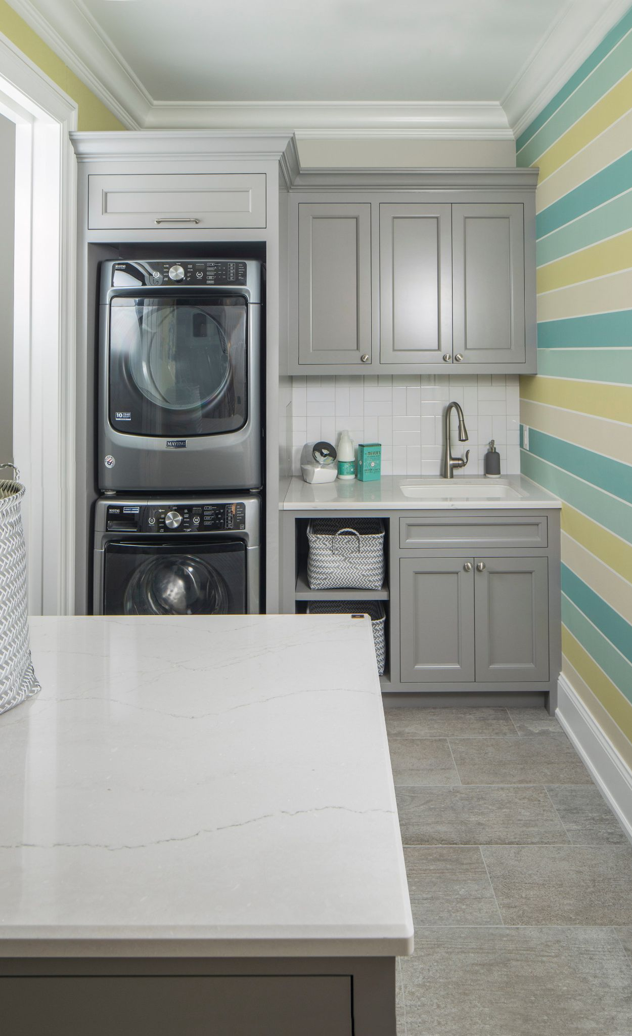 Cambria Ella in a laundry room with blue and green striped walls and gray countertops.