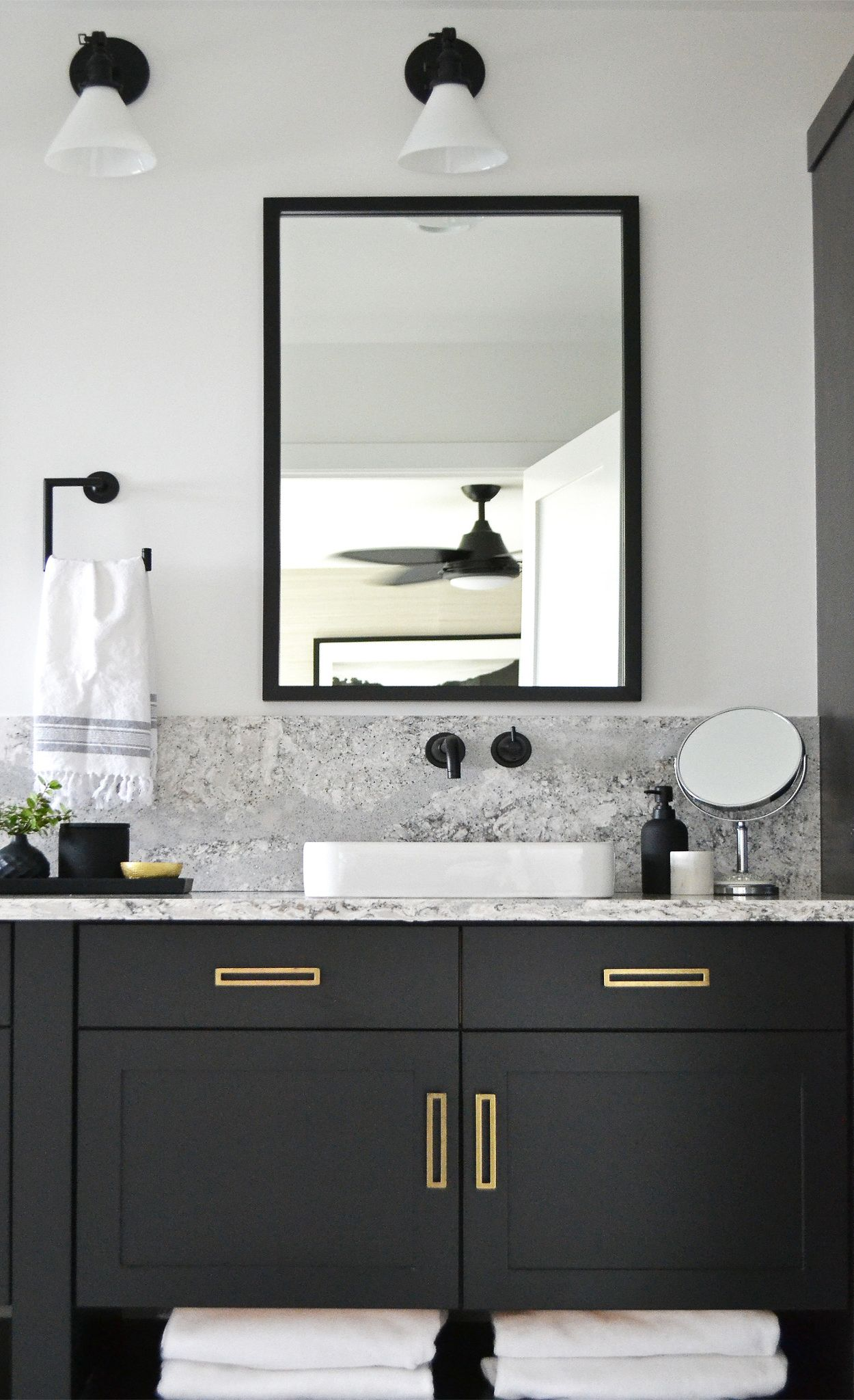Summerhill™ countertops and backsplash with matte black cabinets, faucet, mirror, light fittings, and vanity decor.