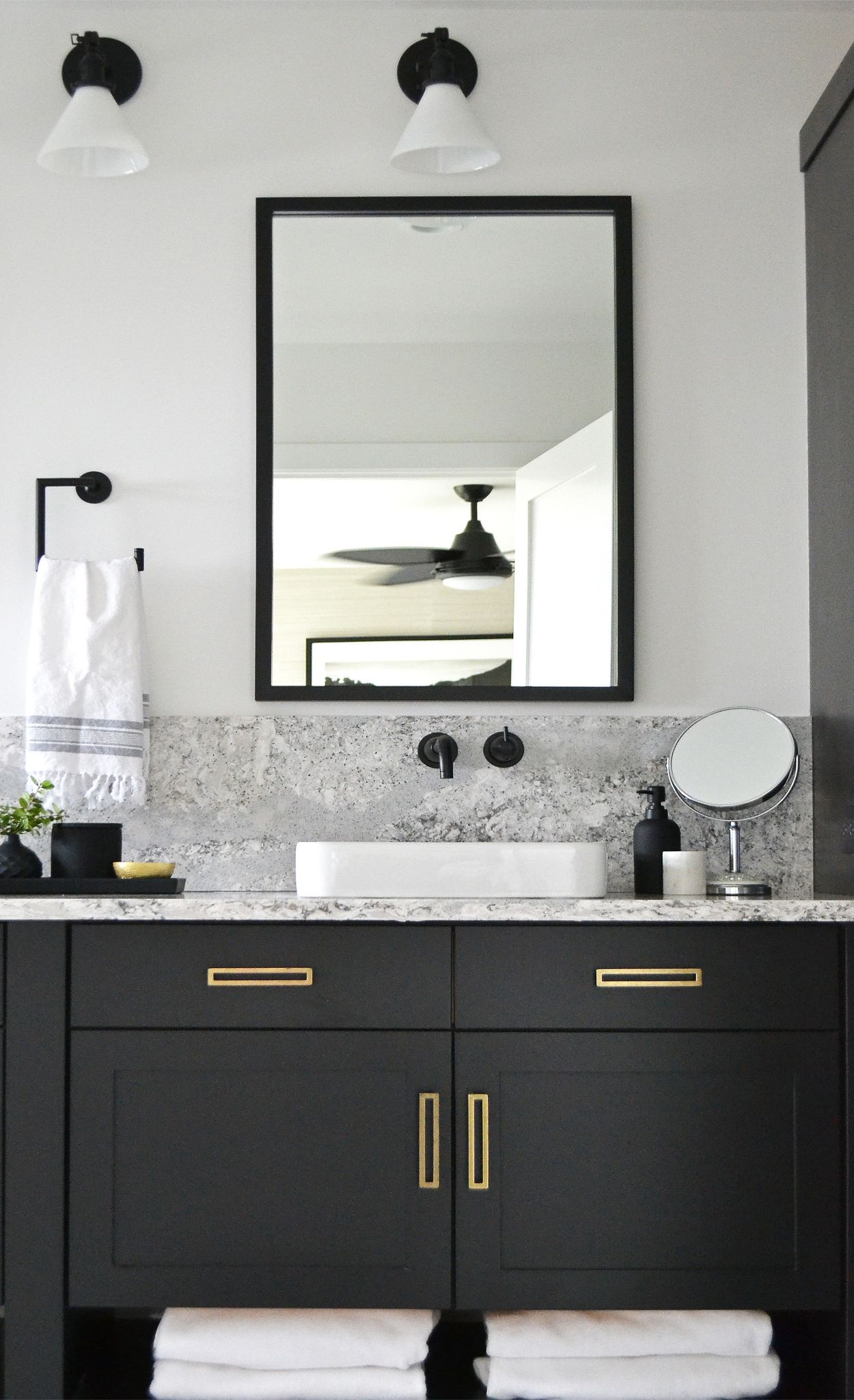Cambria Summerhill  adds a pop of pattern to this matte black bathroom.