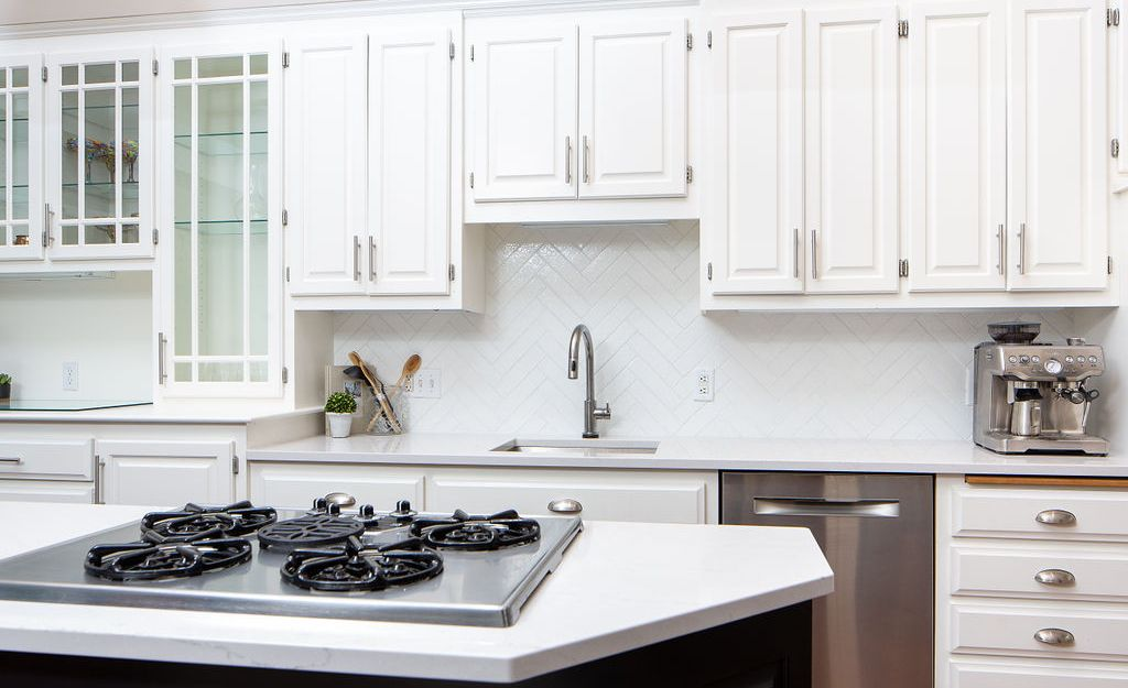 White herringbone tile backsplash paired with Cambria Ella countertops.