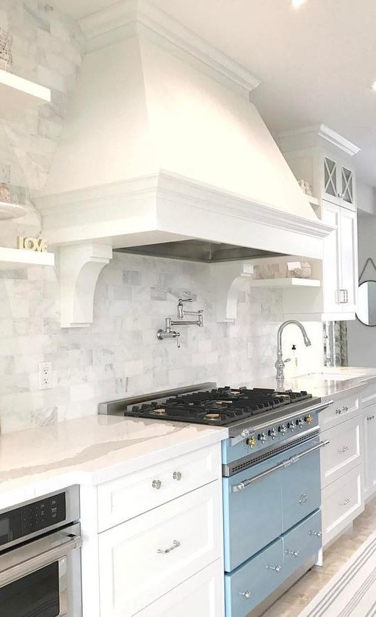 White kitchen with Cambria Brittanicca countertops and light blue range.