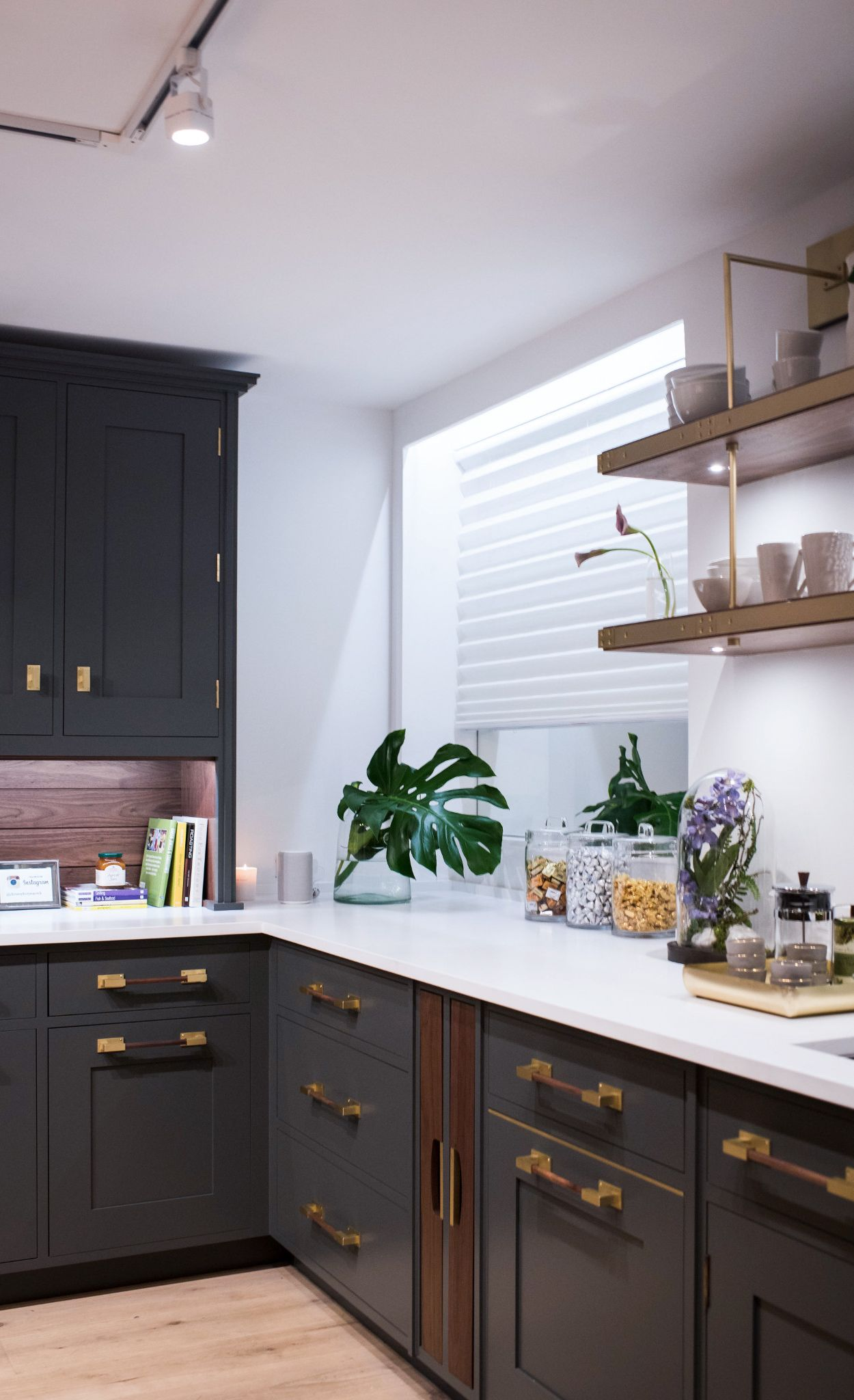 Olive green cabinetry paired with Cambria White Cliff Matte countertops, brass hardware, and open shelving.