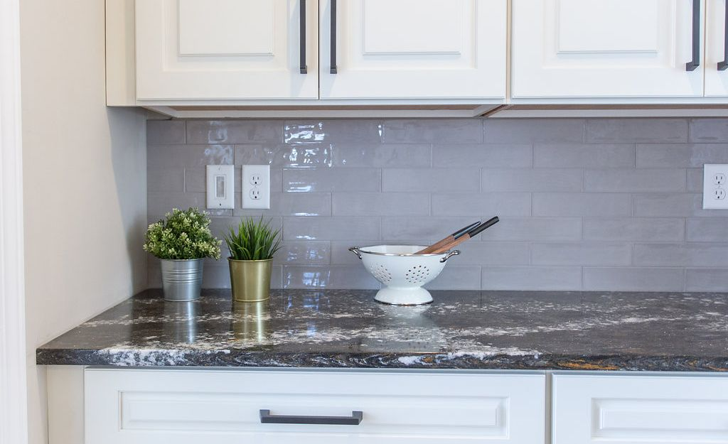 Dark countertop designs like Cambria Ellesmere pair well with soft-gray subway tile.