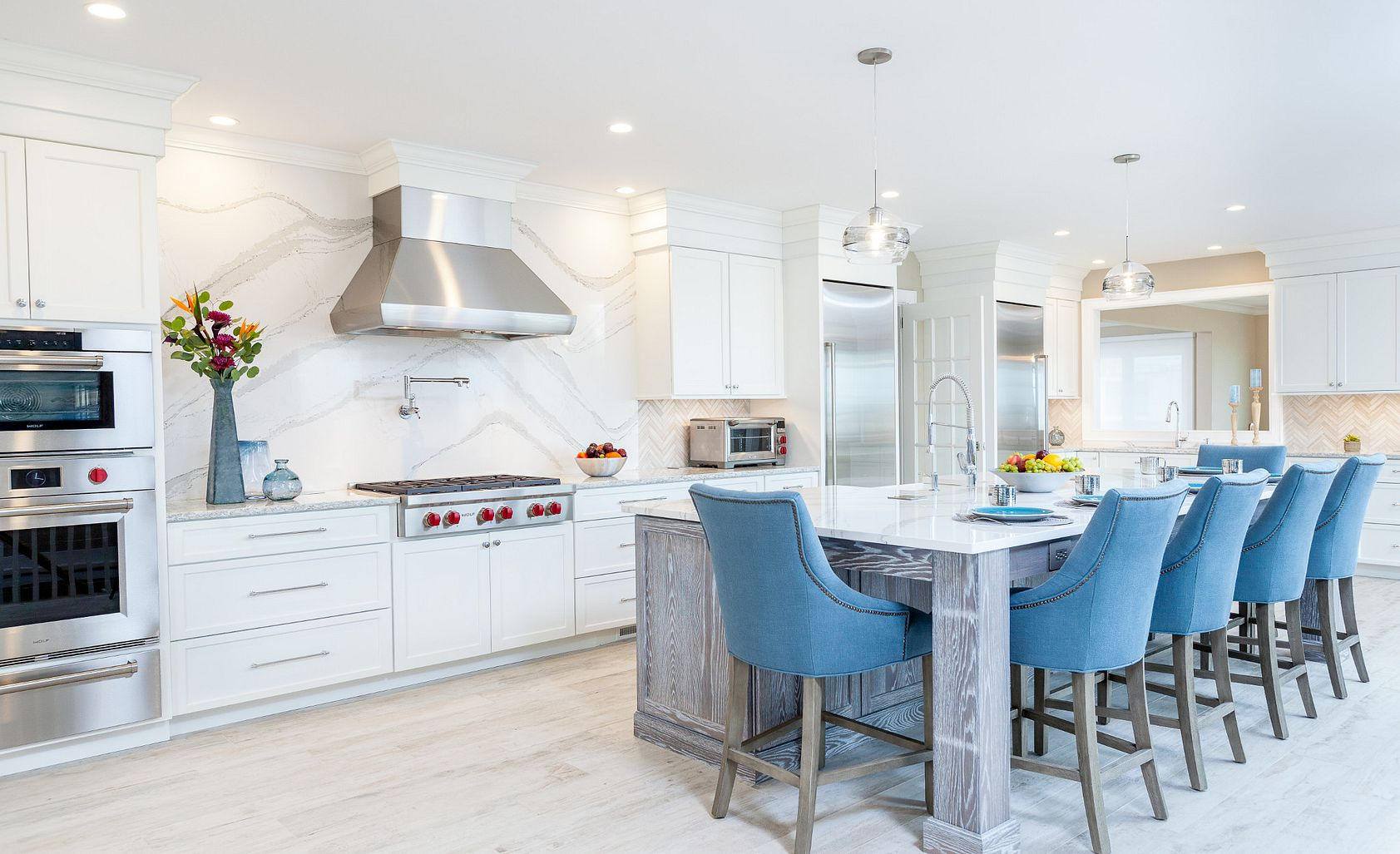 Cambria Brittanicca kitchen island and backsplash with blue stools.