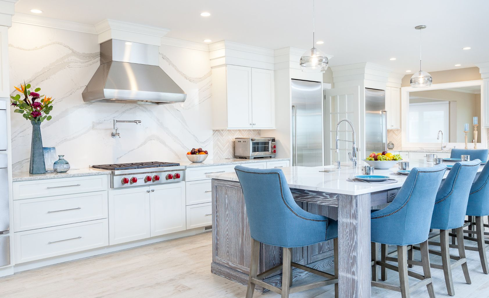 Cambria Brittanicca kitchen island and backsplash with blue stools.