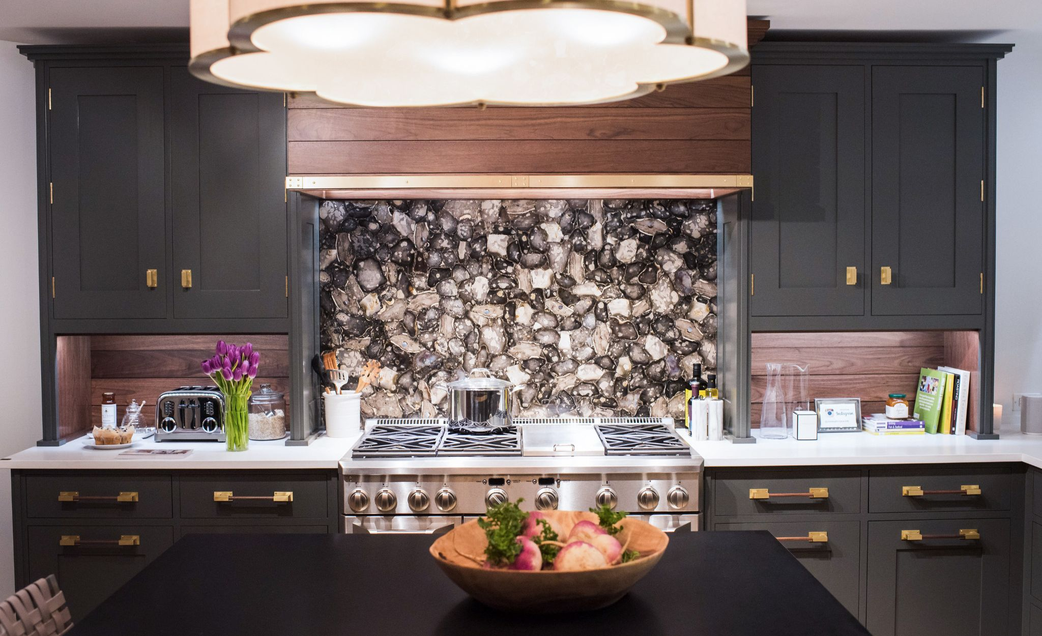 Brass accents create elegant and cohesive kitchen motif, from the hardware to the range hood and light fixture.