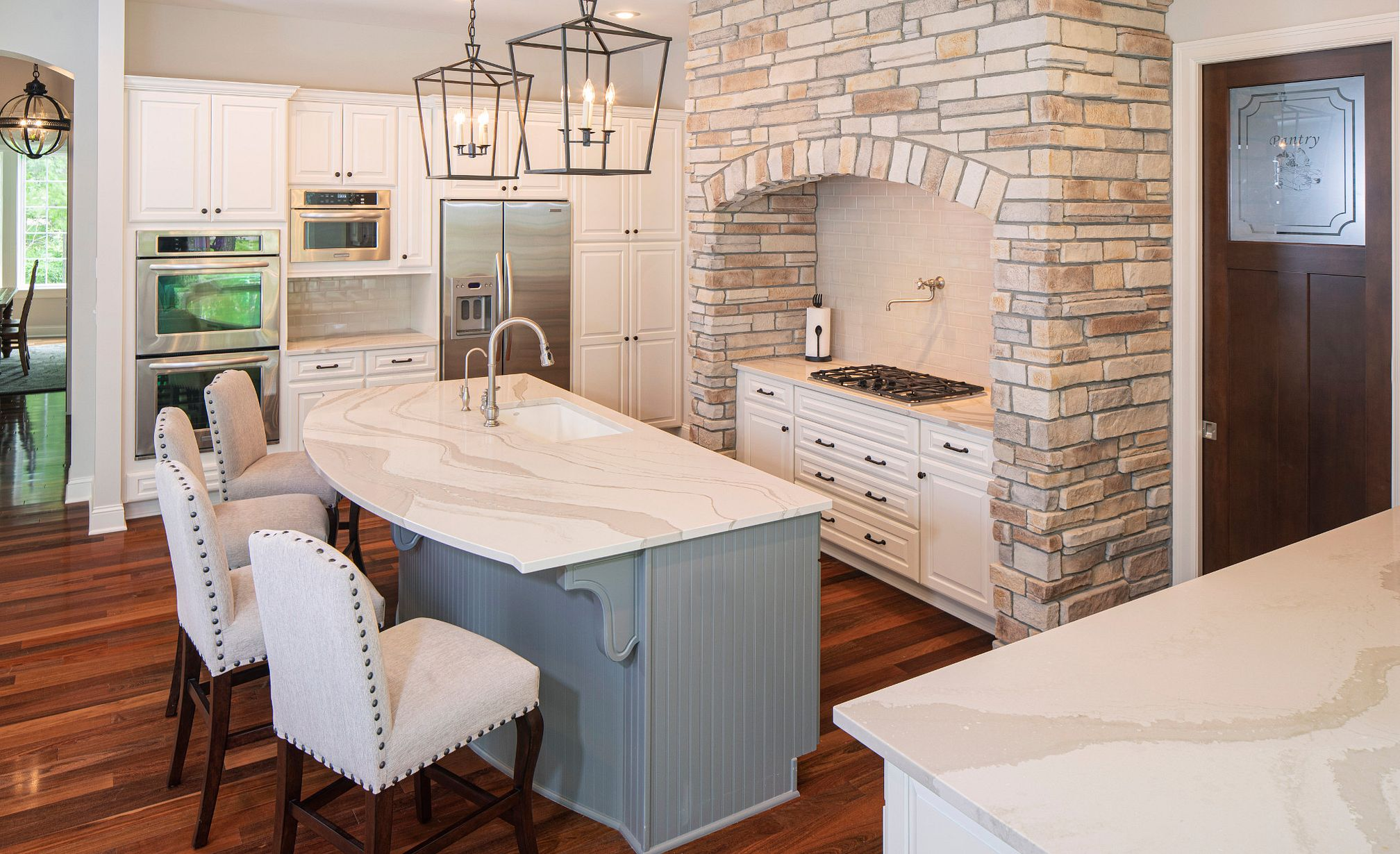 White marble-look quartz countertops in a traditional home with two-tone cabinets and brick accent.