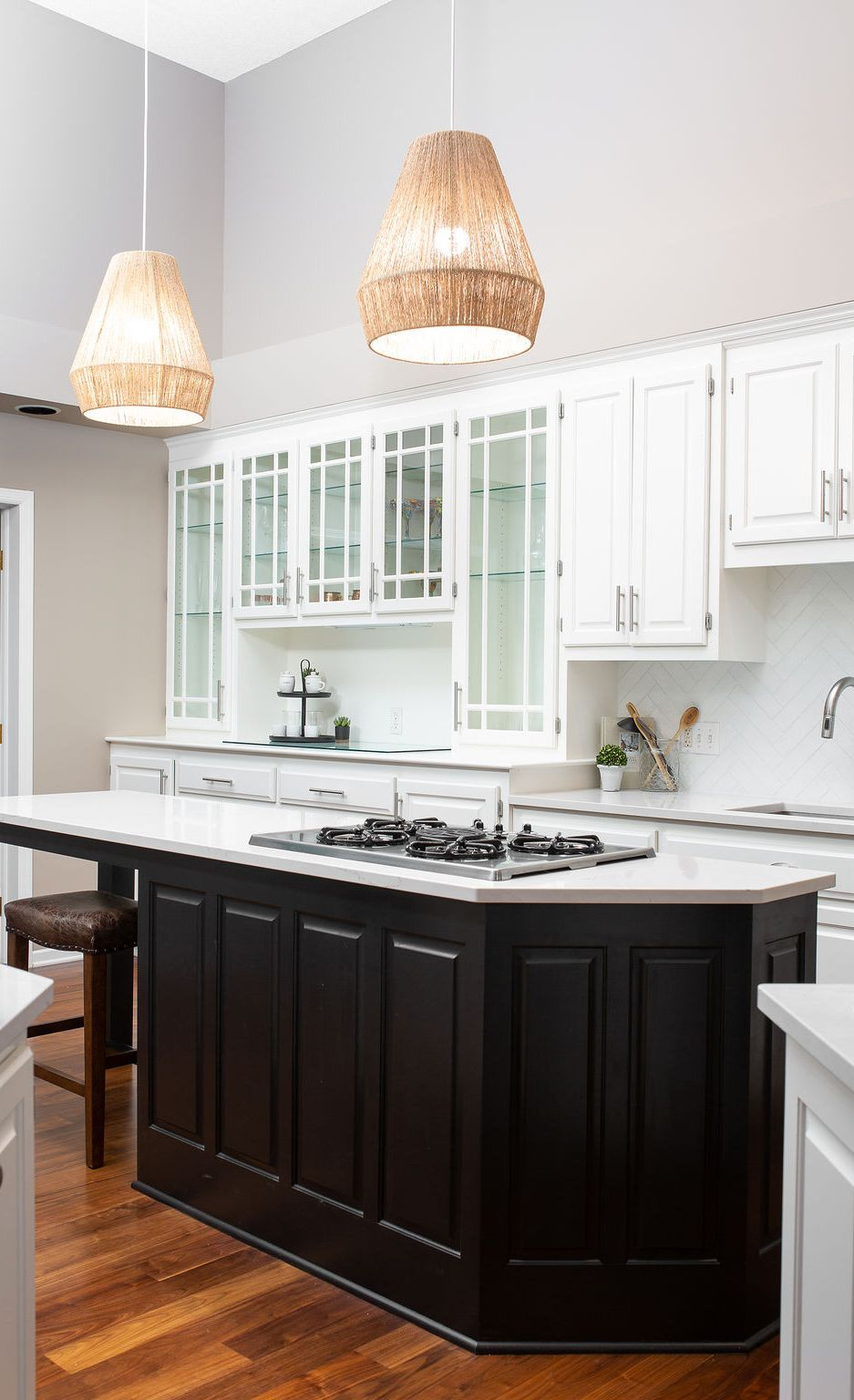 Pendant lights and dark cabinetry create a focal point for the Ella-topped kitchen island.