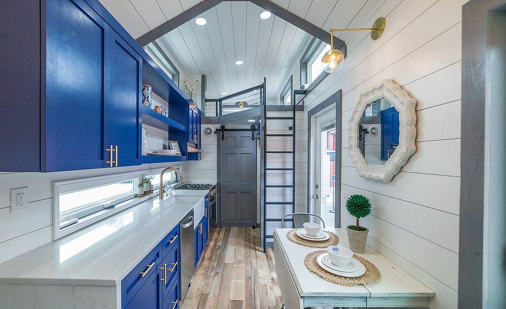 Small space kitchen with cobalt blue cabinets, Cambria Ella countertops, and white shiplap ceiling and walls.