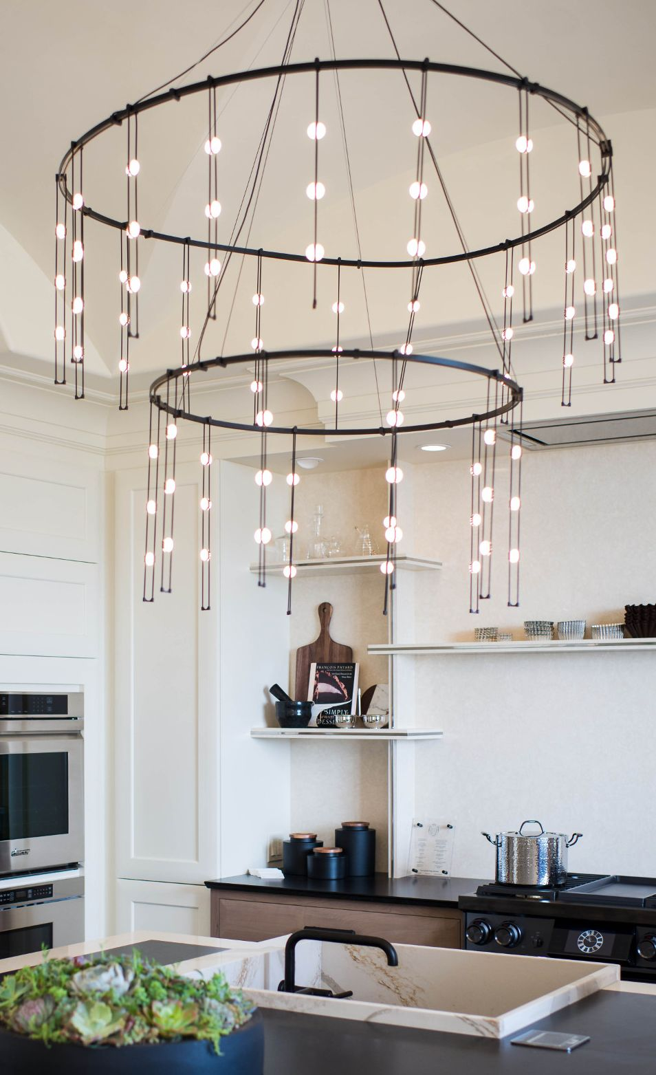 A modern chandelier illuminates the kitchen island in the Kips Bay Decorator Show House Palm Beach.