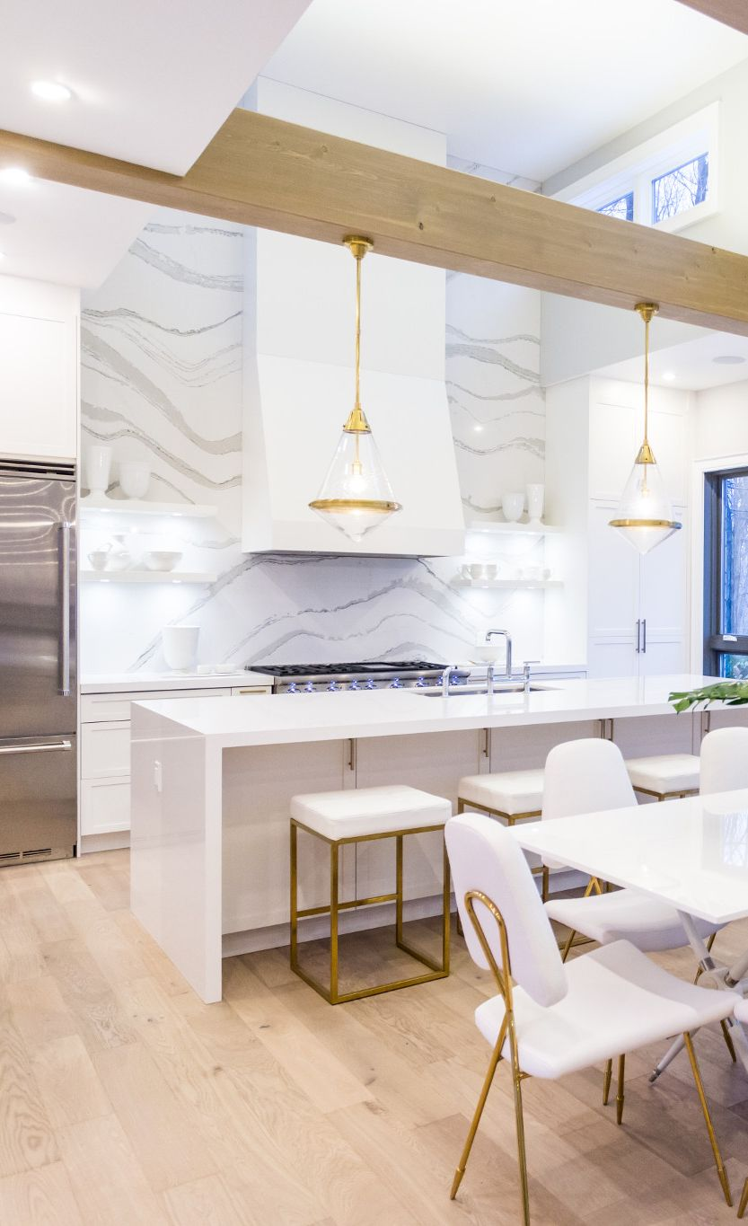 Cambria Brittanicca full-height backsplash in a white and gold kitchen.